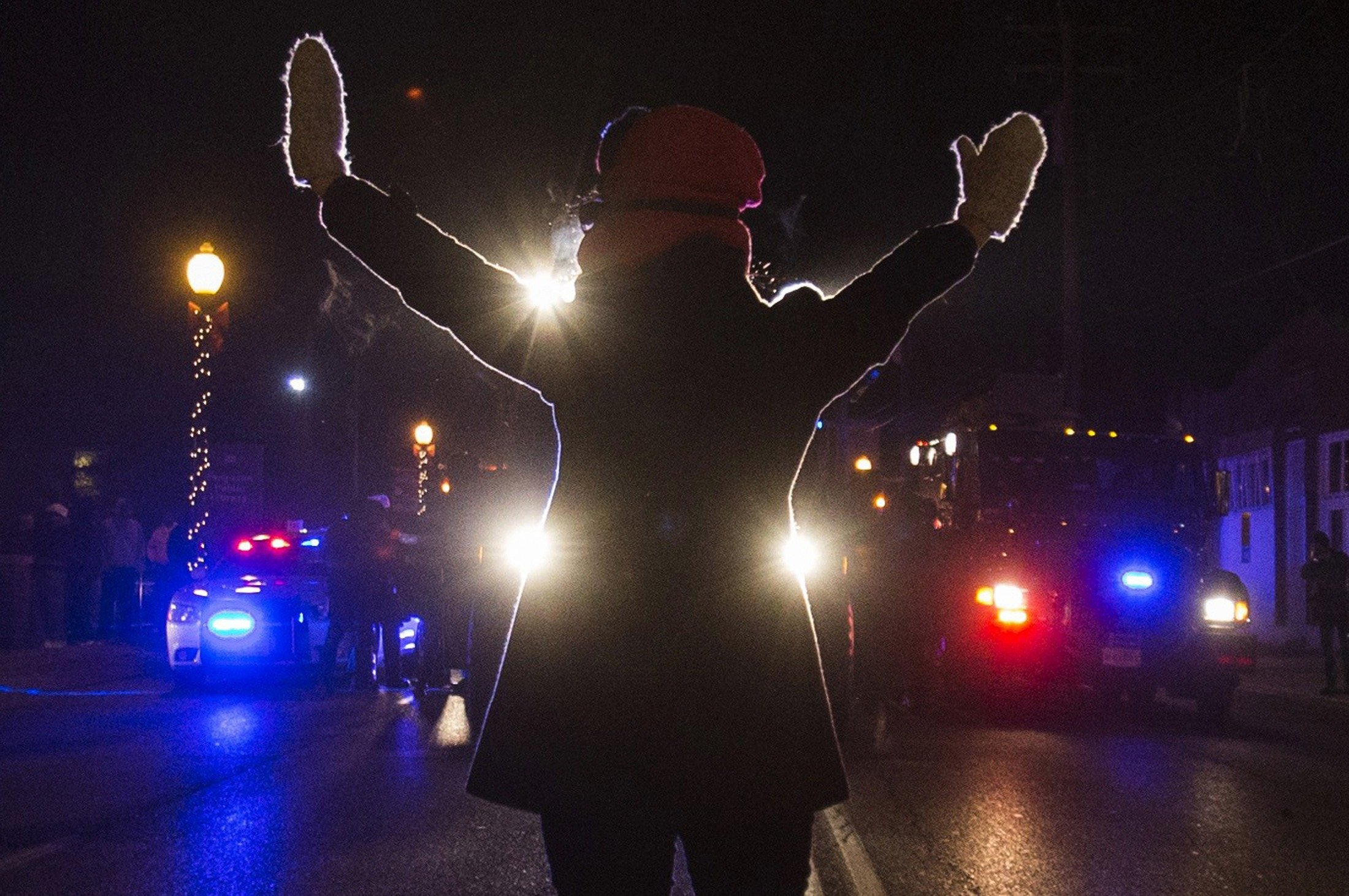 A female protester raises her hands while blocking police cars in Ferguson, Mo. on Nov. 25, 2014.