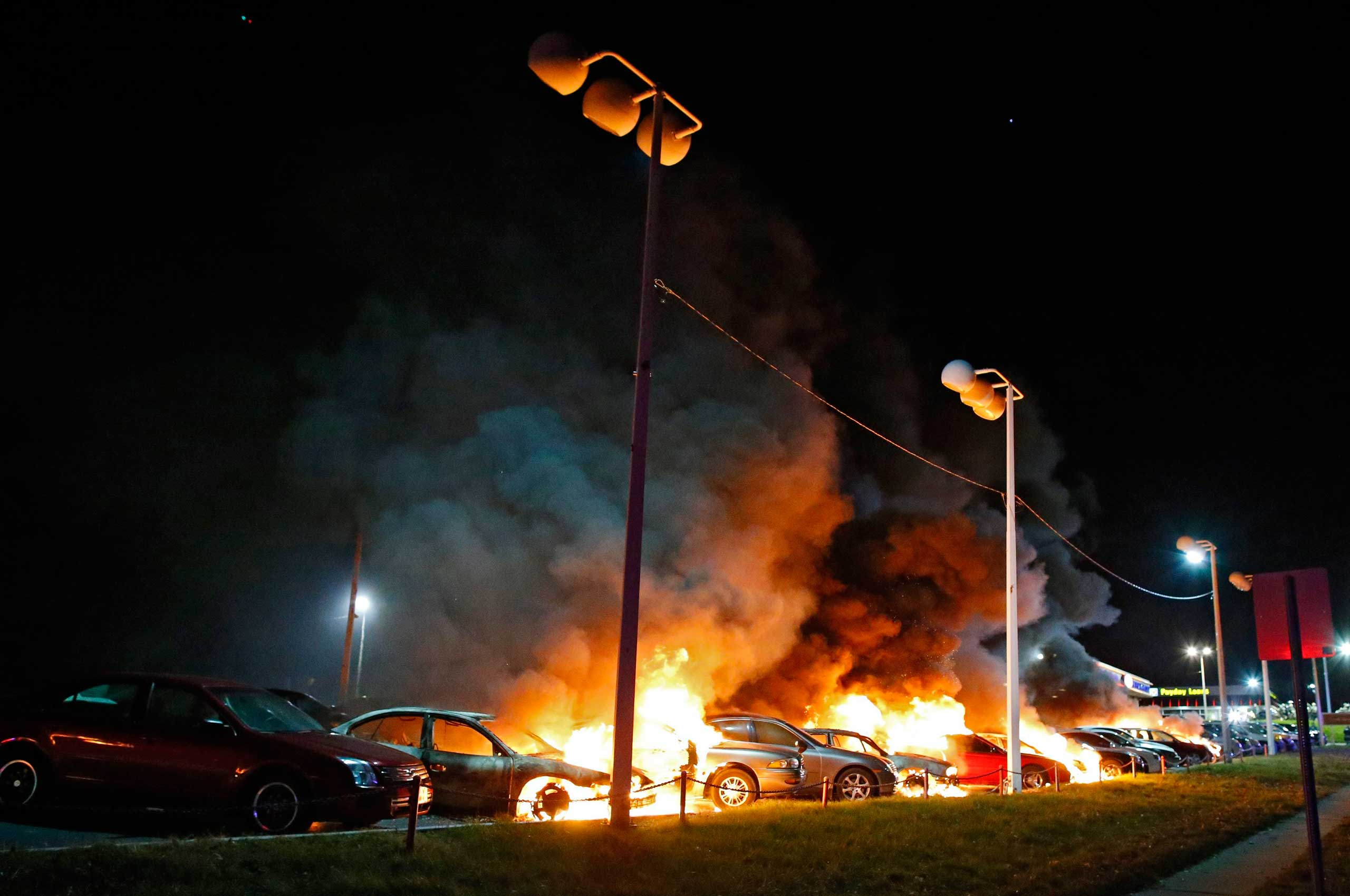 Cars burn at a car dealership as demonstrators protest the Grand Jury decision not to indict police officer Darren Wilson over the shooting death of Michael Brown in Ferguson, Mo. on No.v 24, 2014.