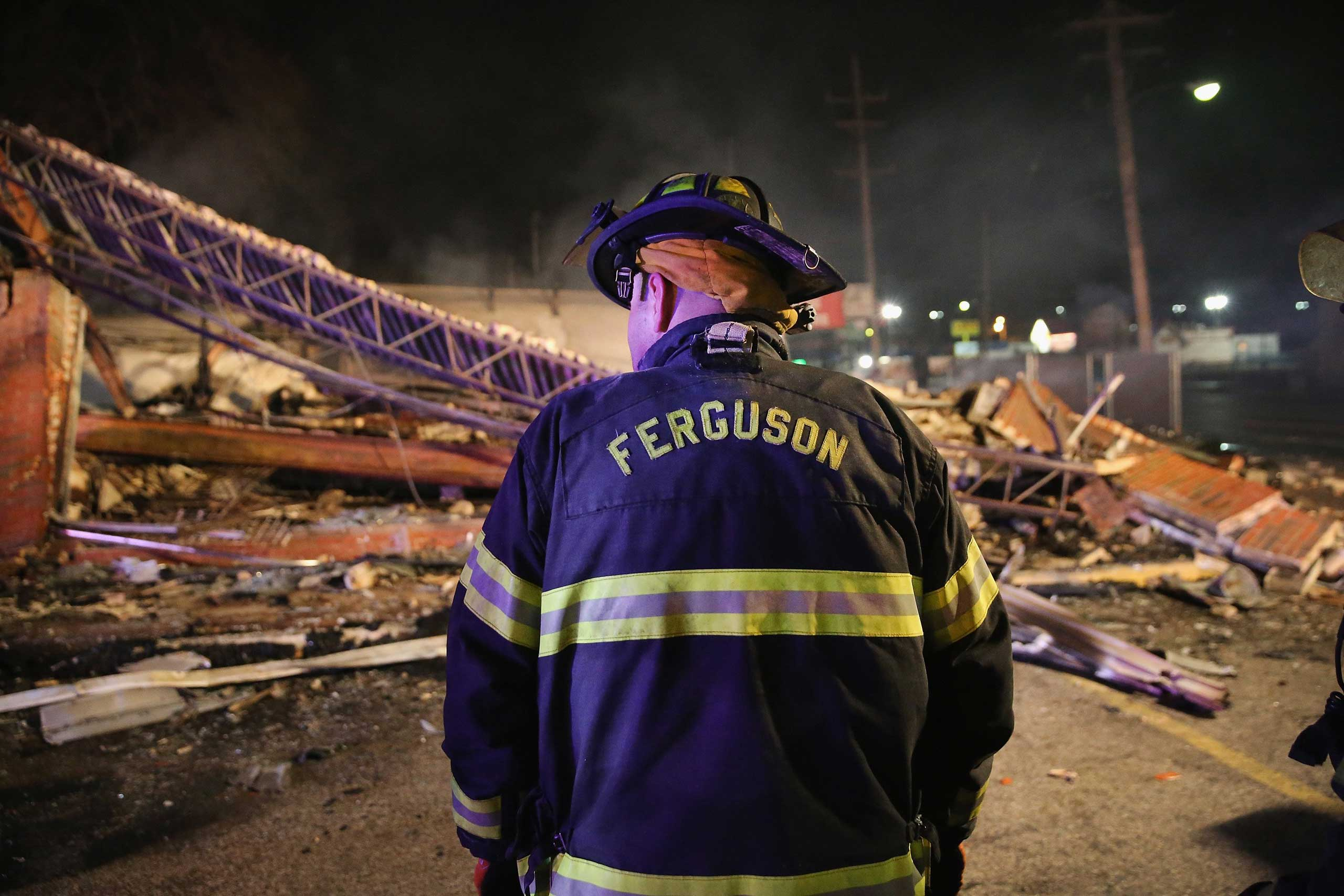 A Ferguson firefighter surveys rubble at a strip mall that was set on fire when rioting erupted following the grand jury announcement in the Michael Brown case on Nov. 25, 2014 in Ferguson, Mo.