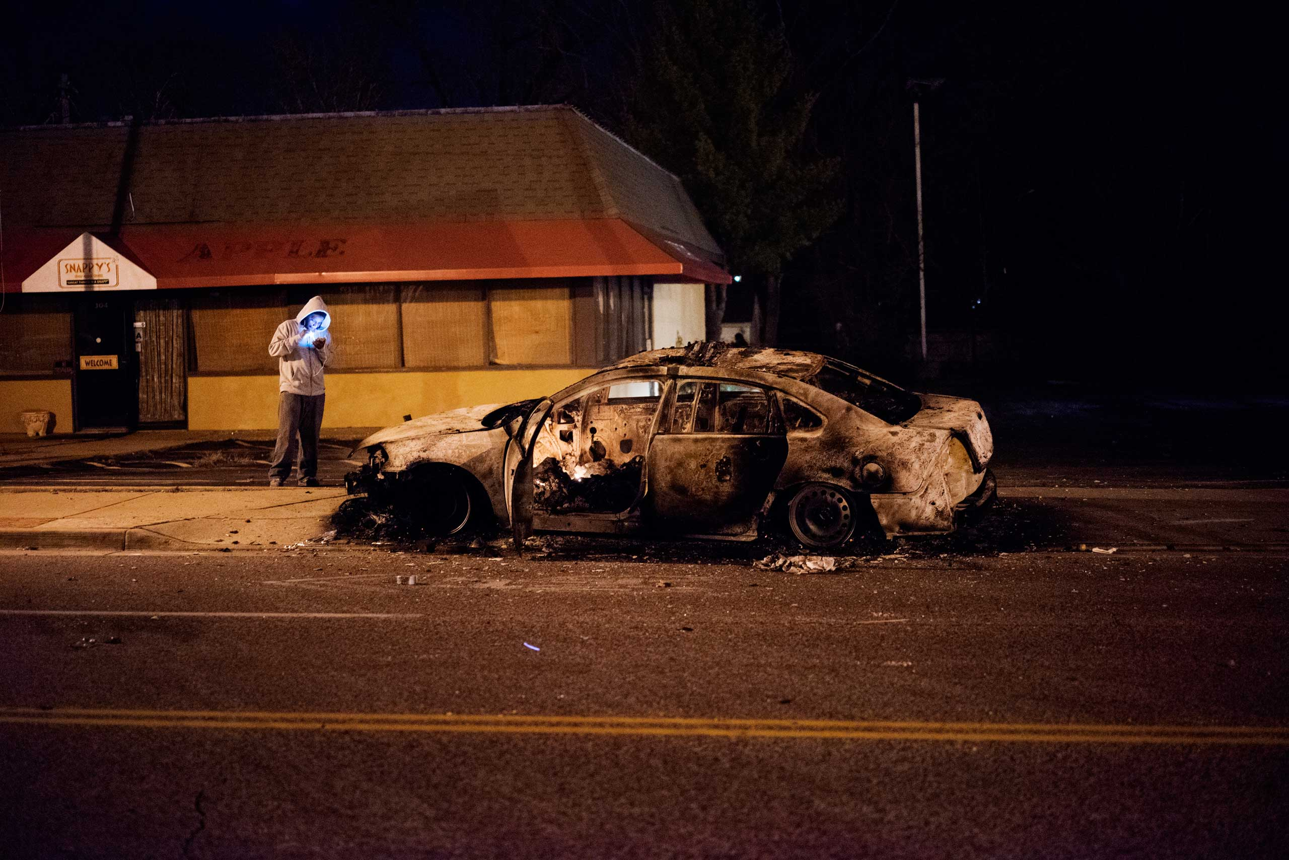 A man stands by a burned out car in Ferguson, Mo. on Nov. 24, 2014