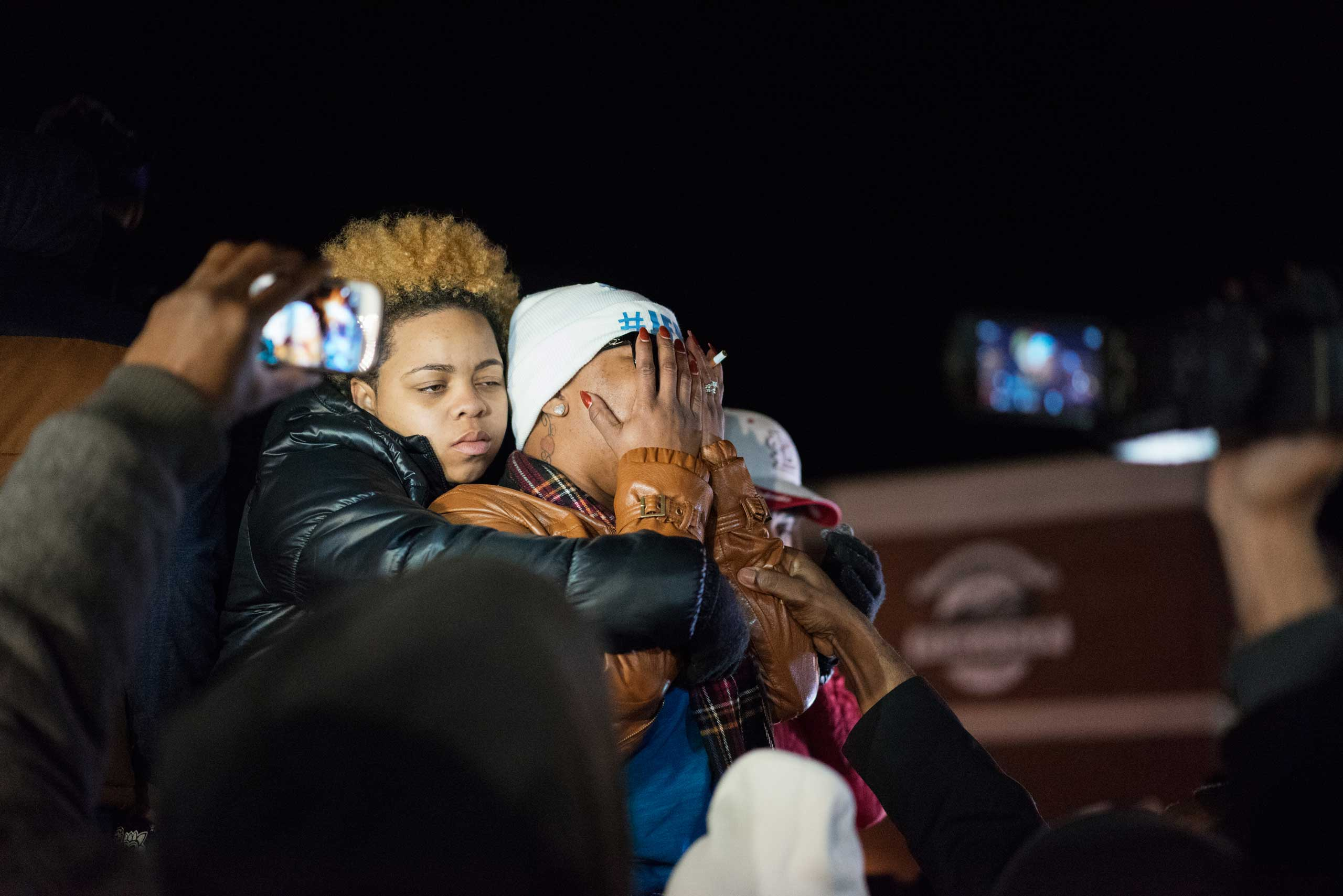 Michael Brown's mother, Lesley McSpadden, covers her face while standing alongside other demonstrators in Ferguson, Mo. on Nov. 24, 2014