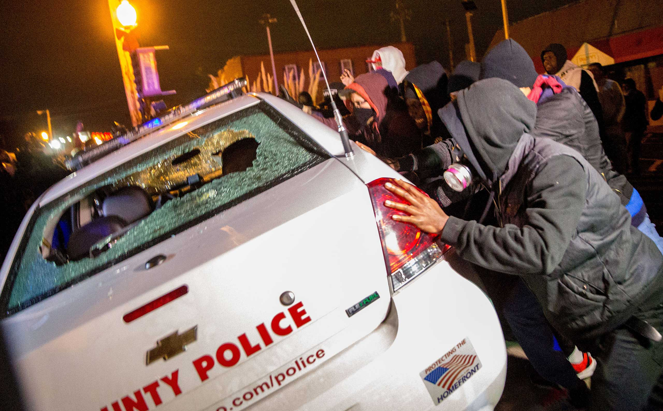 Demonstrators attempt to push over a police car in Ferguson, Mo. on Nov, 24, 2014.