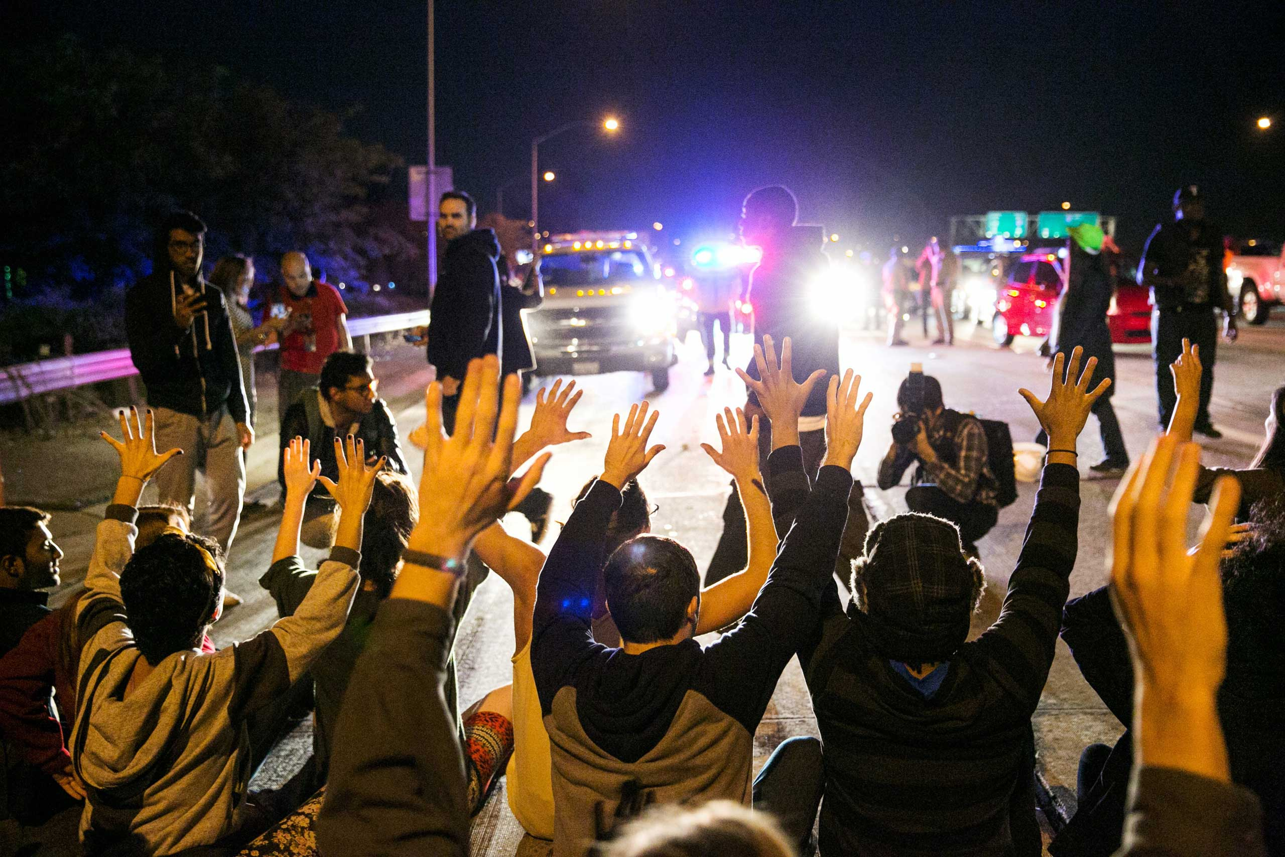 Protesters raise their hands and sit on the ground to block traffic on the 110 Freeway in Los Angeles on Nov. 25, 2014.