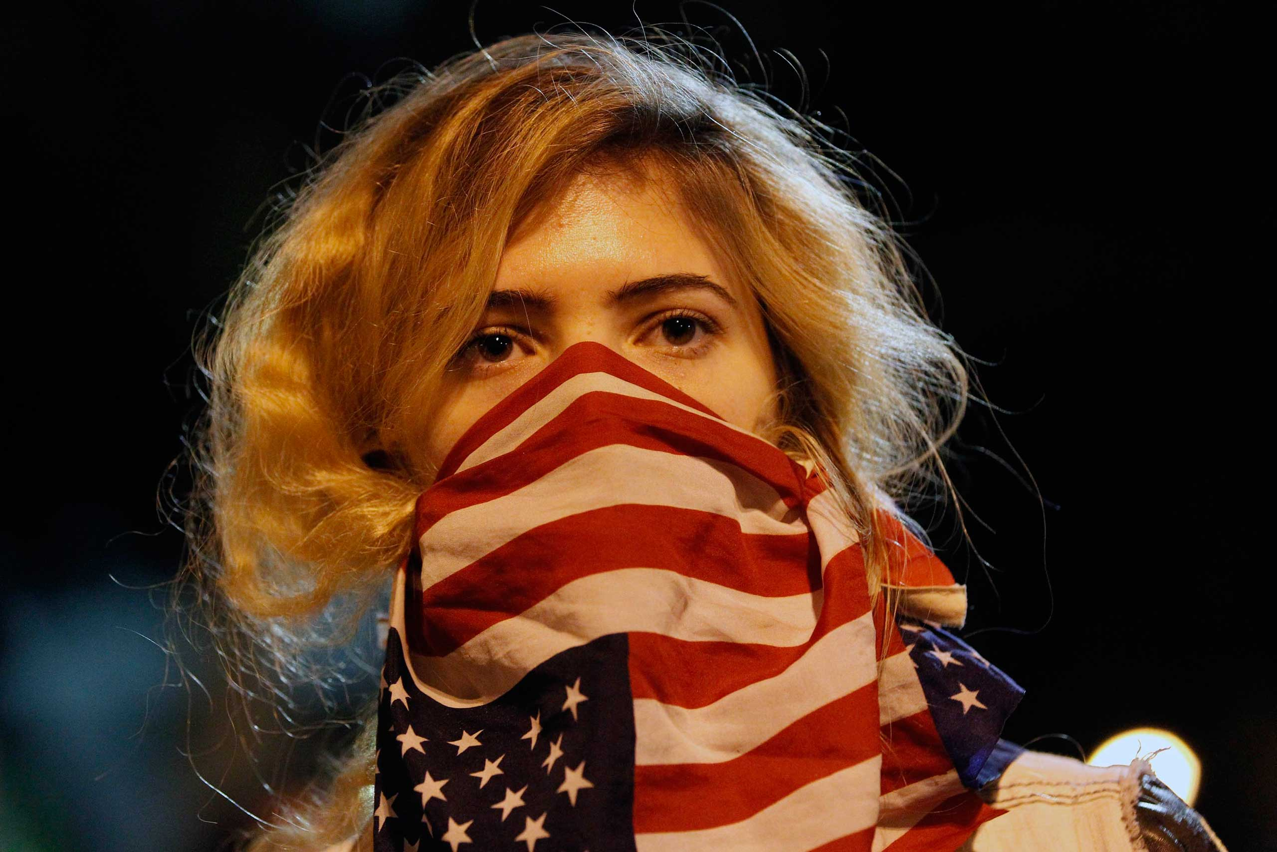 A woman wears a U.S. flag in front of her face during a rally at Los Angeles Police Department headquarters in downtown Los Angeles on Nov. 25, 2014.