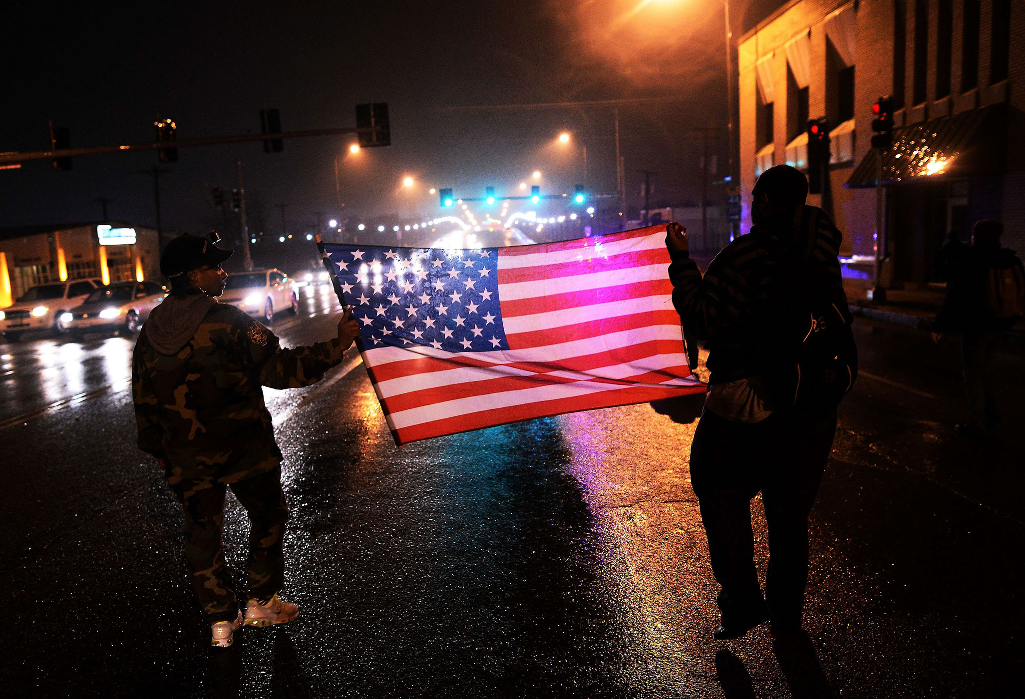 Two demonstrators march with a U.S. flag in St. Louis on Nov. 23, 2014, to protest the death of 18-year-old Michael Brown