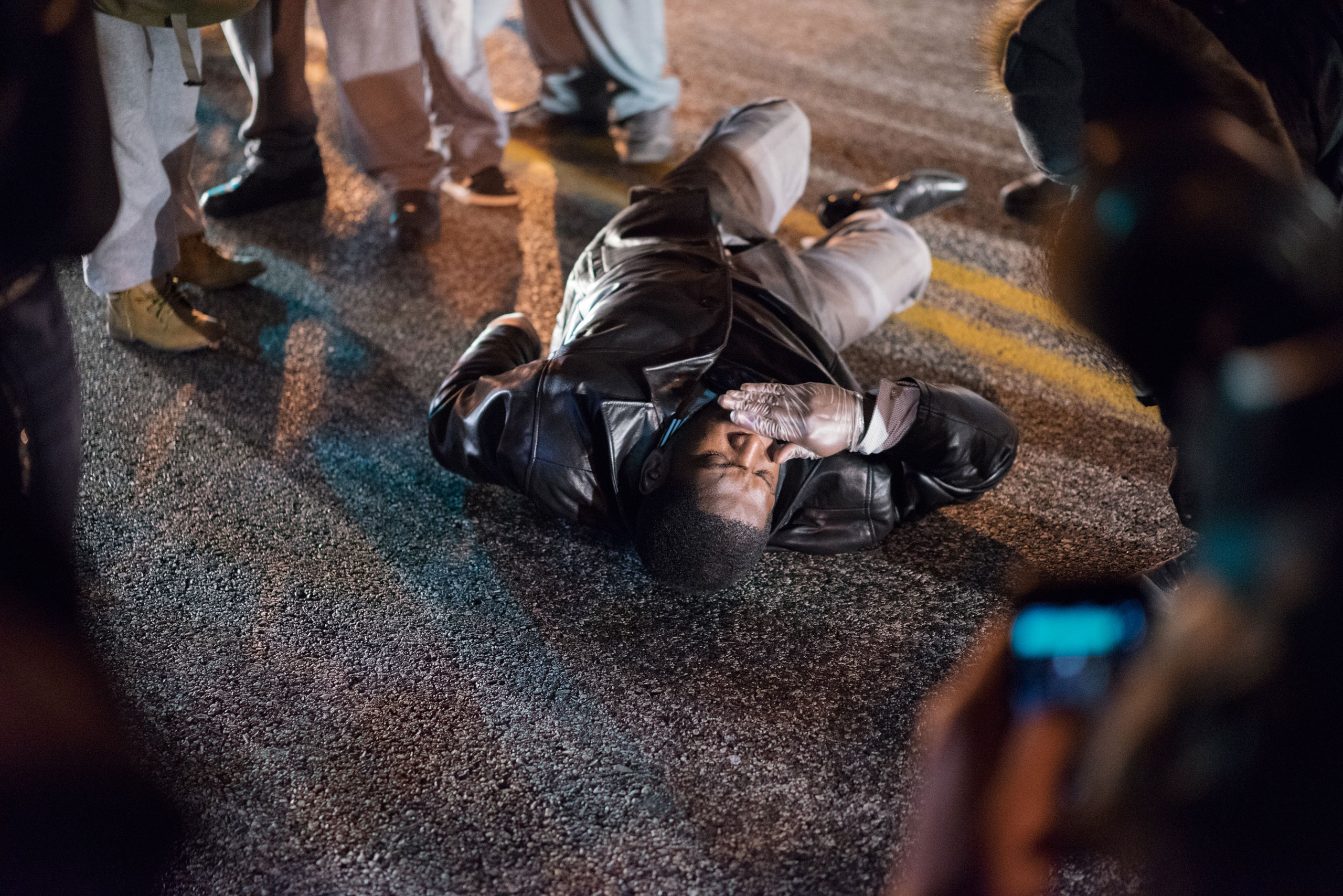 A man lies on the ground amid protests in Ferguson, Mo. on Nov. 24, 2014