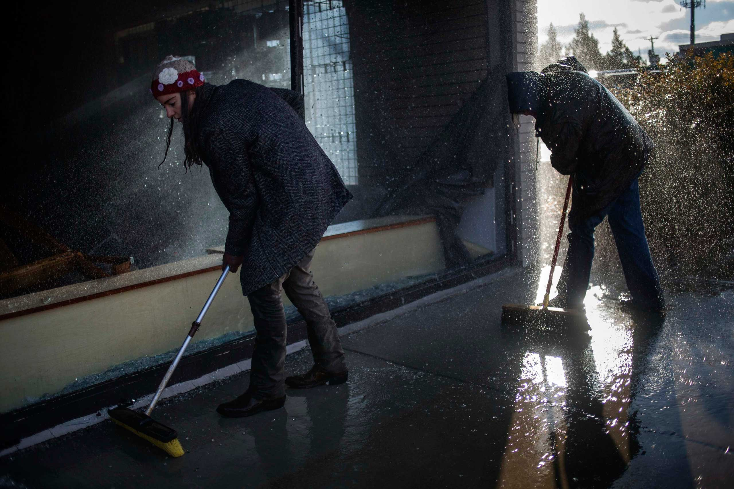 Volunteers, drenched from a smoke alarm, assist in clearing broken glass outside a burned and looted shop in Ferguson, Mo. on Nov. 25, 2014.