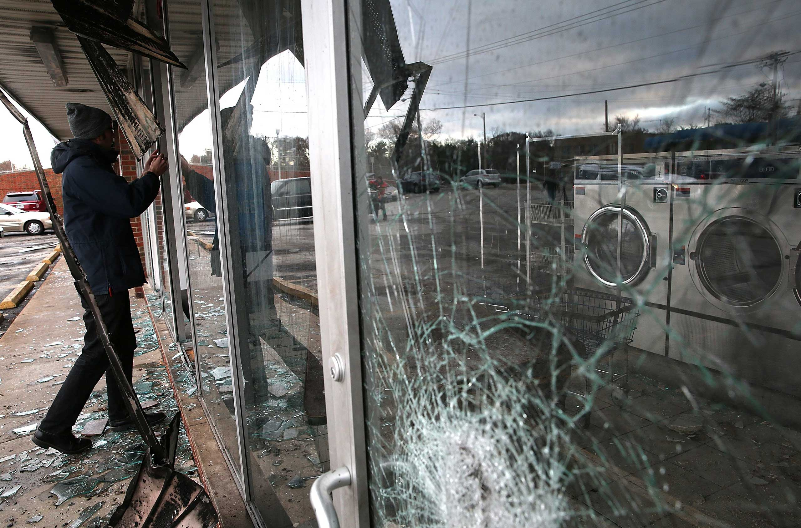 A reporter looks through the window of a laundromat that was damaged during a demonstration in Dellwood, Mo. on Nov. 25, 2014.