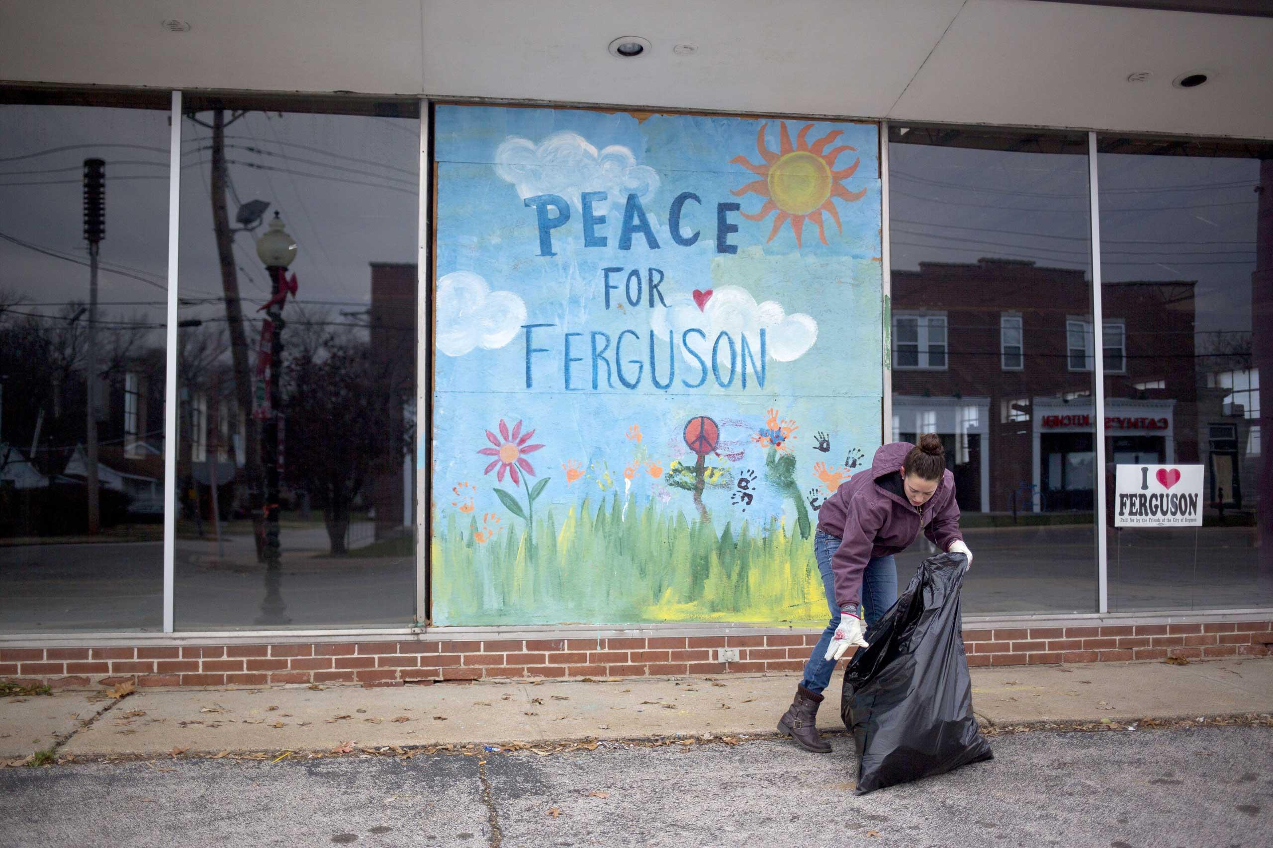 Jodi Wurm helps to  clean up after violent protests damaged businesses in Ferguson, Mo., Nov. 25, 2014.