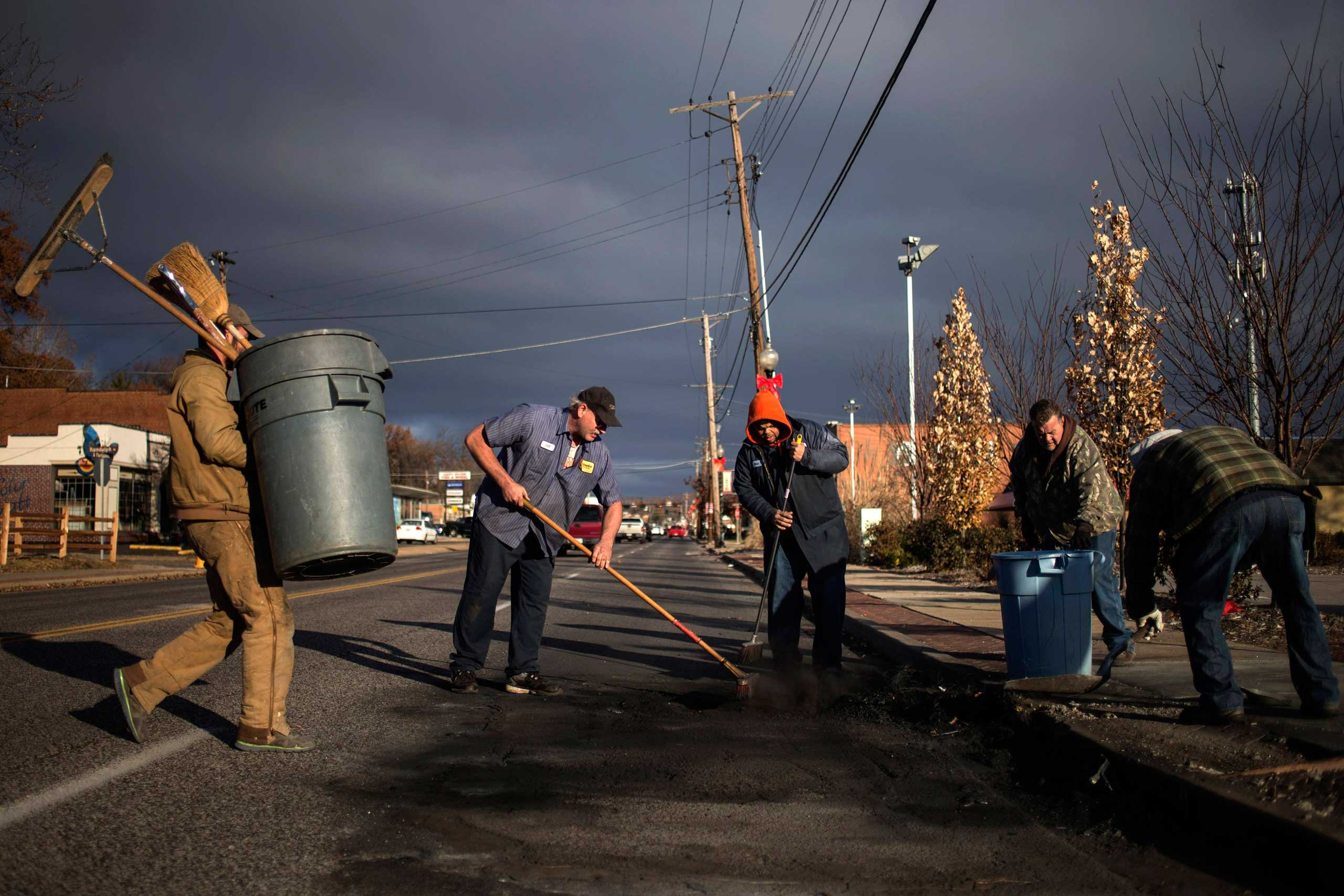 Volunteers and workers clear soot from the site where a police vehicle was set ablaze in Ferguson, Mo. on Nov. 25, 2014.