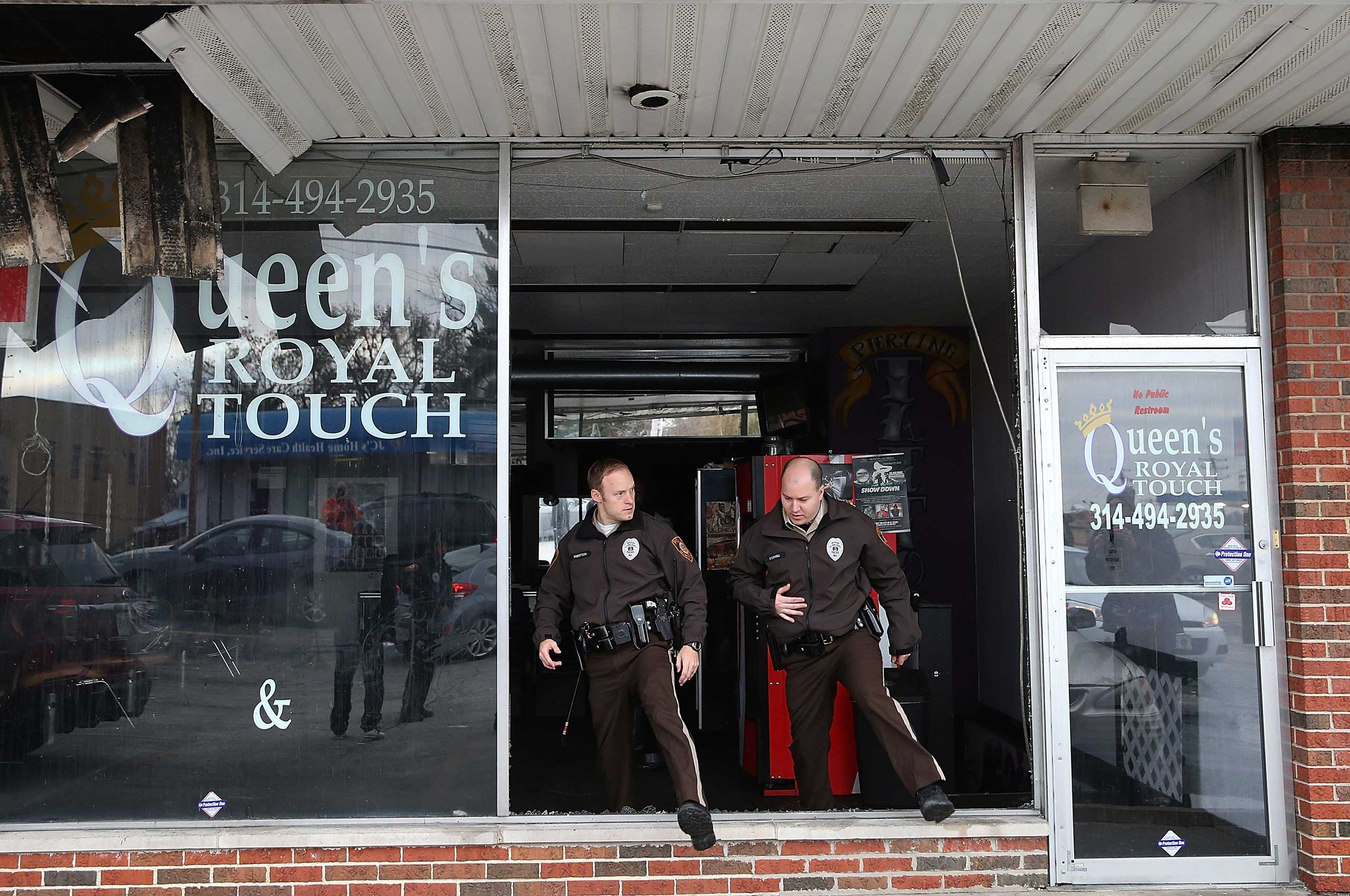 St. Louis County police officers search a business in a building that was burned during a demonstration in Dellwood, Mo. on Nov. 25, 2014.