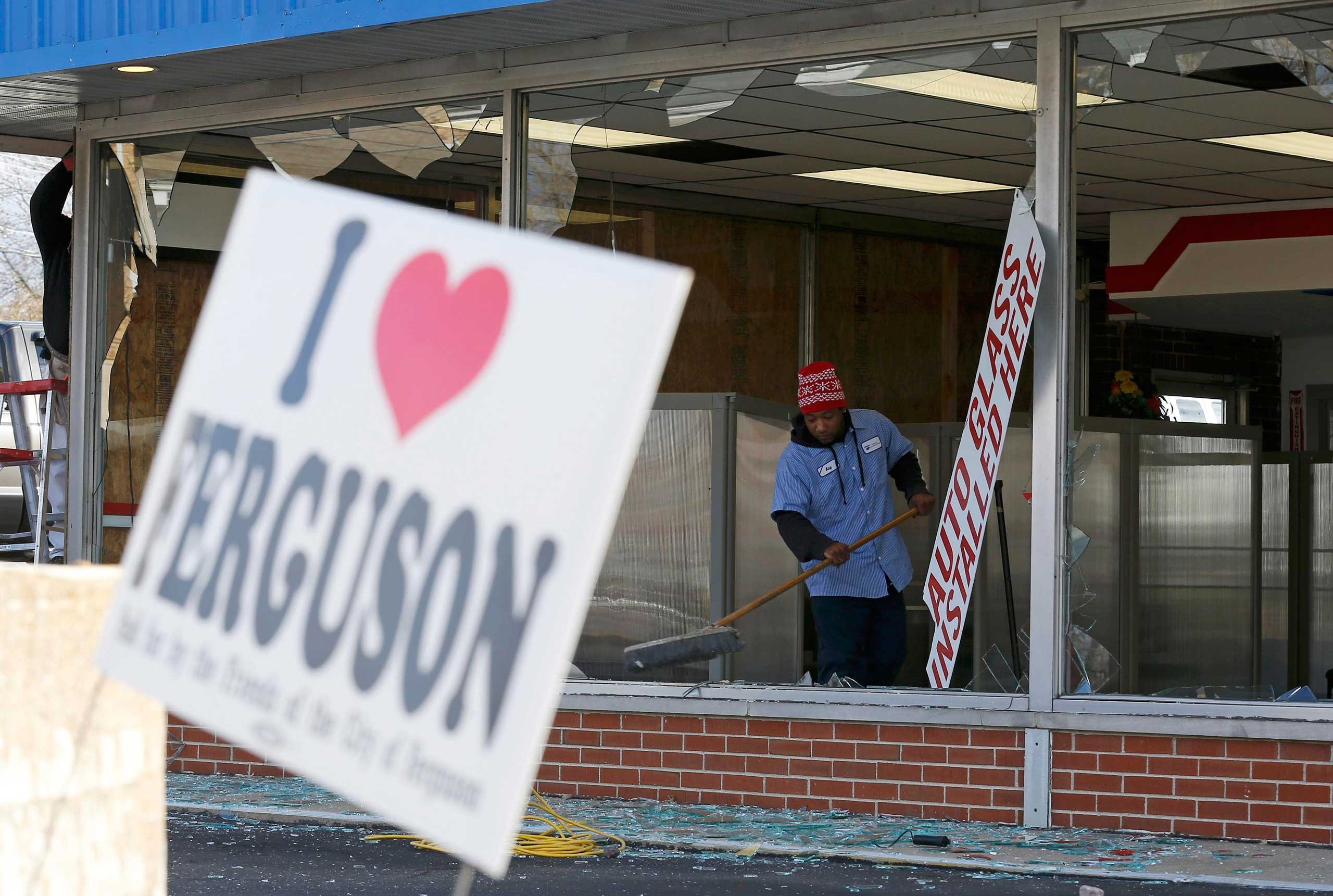 People clean up a business that was damaged in riots the previous night in Ferguson, Mo. on Nov. 25, 2014.