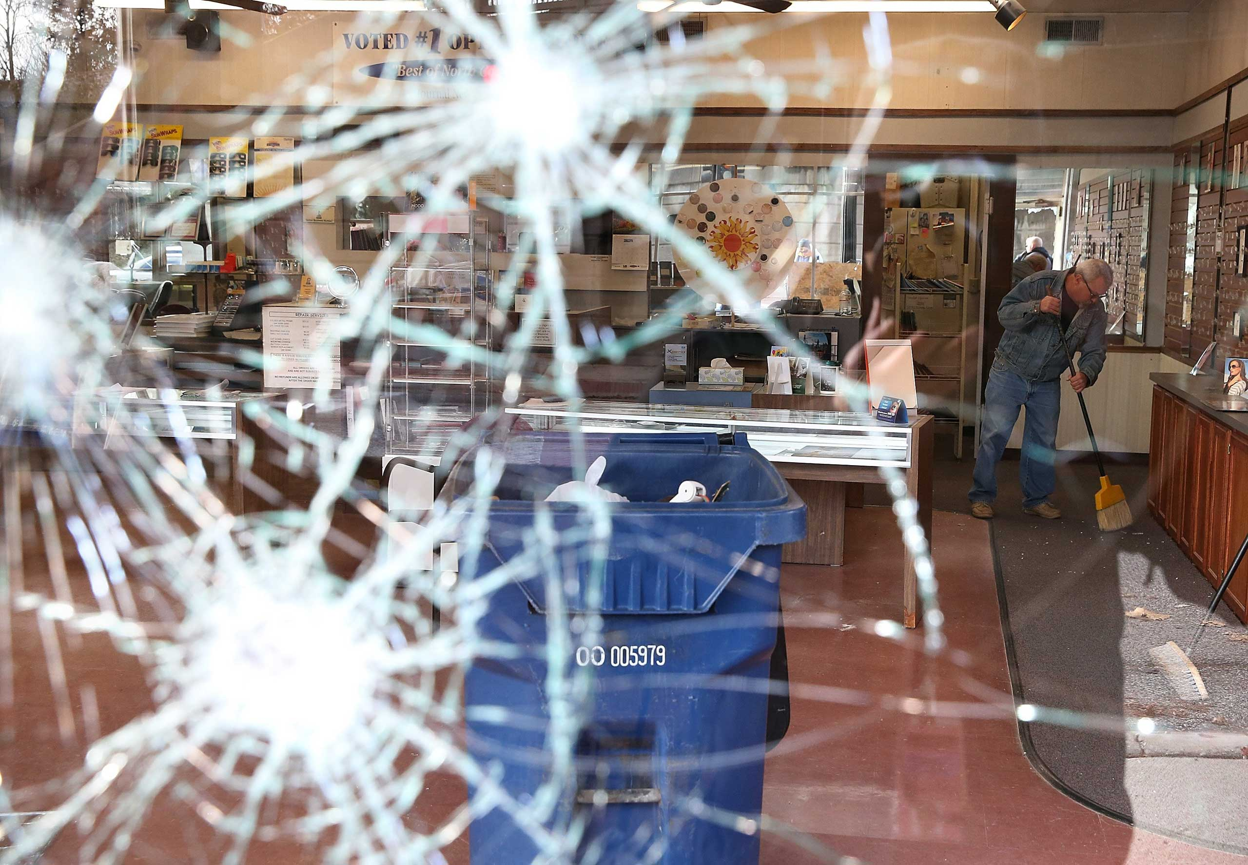 A worker cleans up glass at a business that was damaged during a demonstration in Ferguson, Mo. on Nov. 25, 2014.