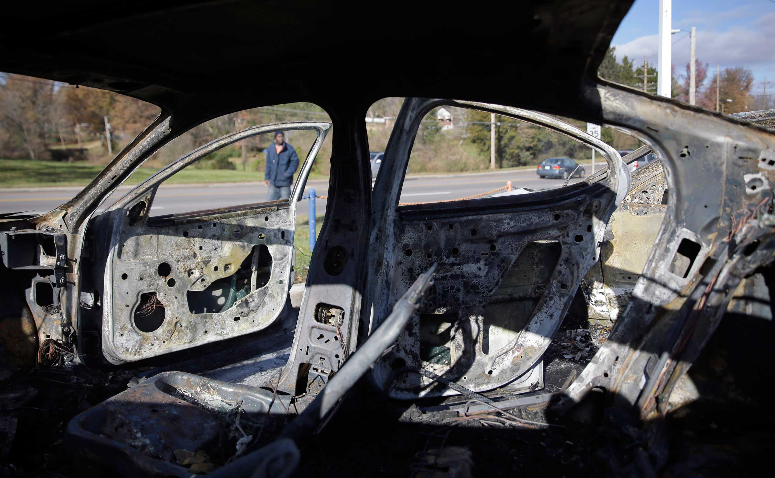 A man walks past a row of charred vehicles on the lot of a used car dealership in Dellwood, Mo. on Nov. 25, 2014.