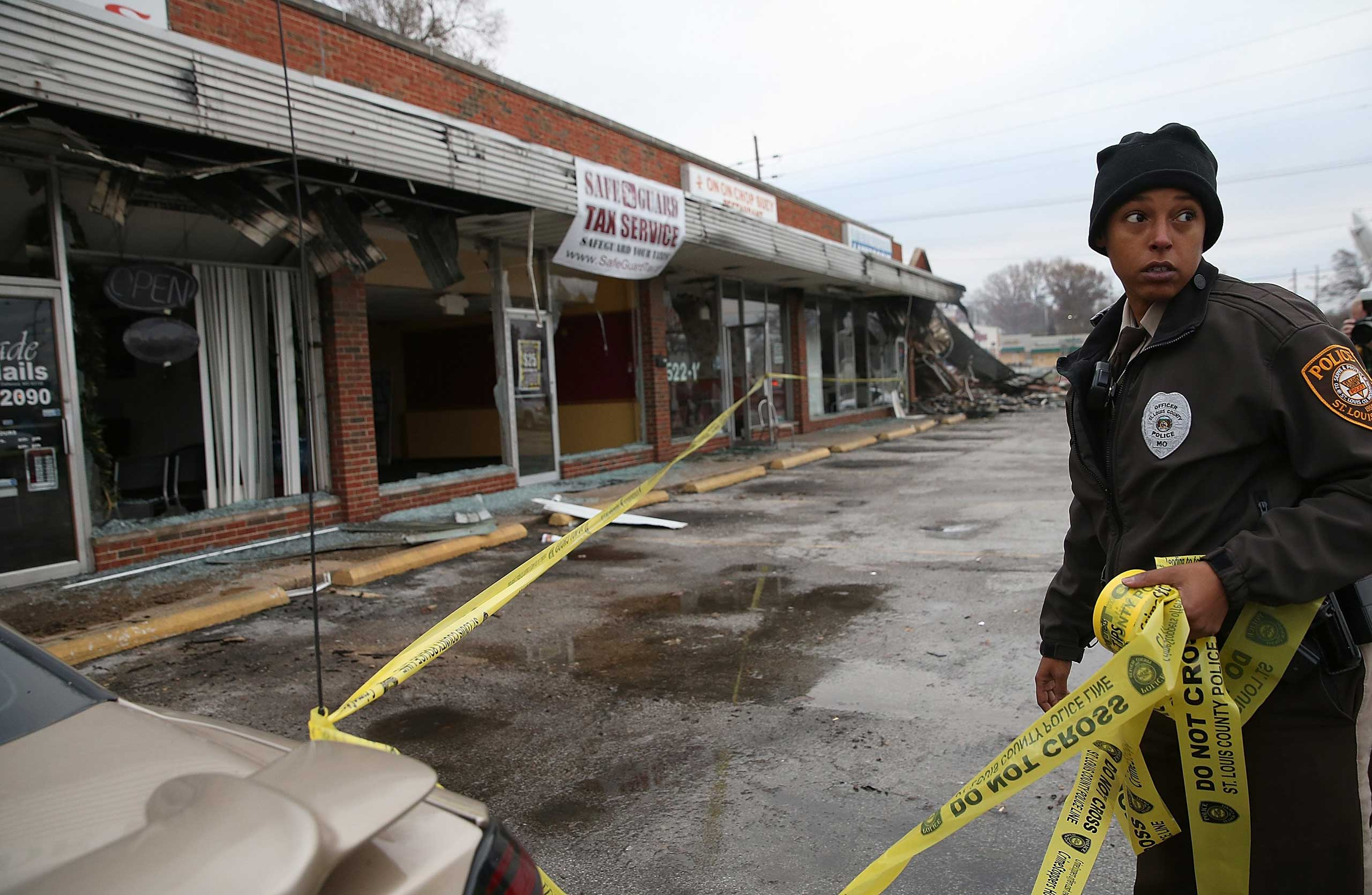 A St. Louis County police officer uses official tape to secure a building that was burned during a demonstration in Dellwood, Mo. on Nov. 25, 2014.