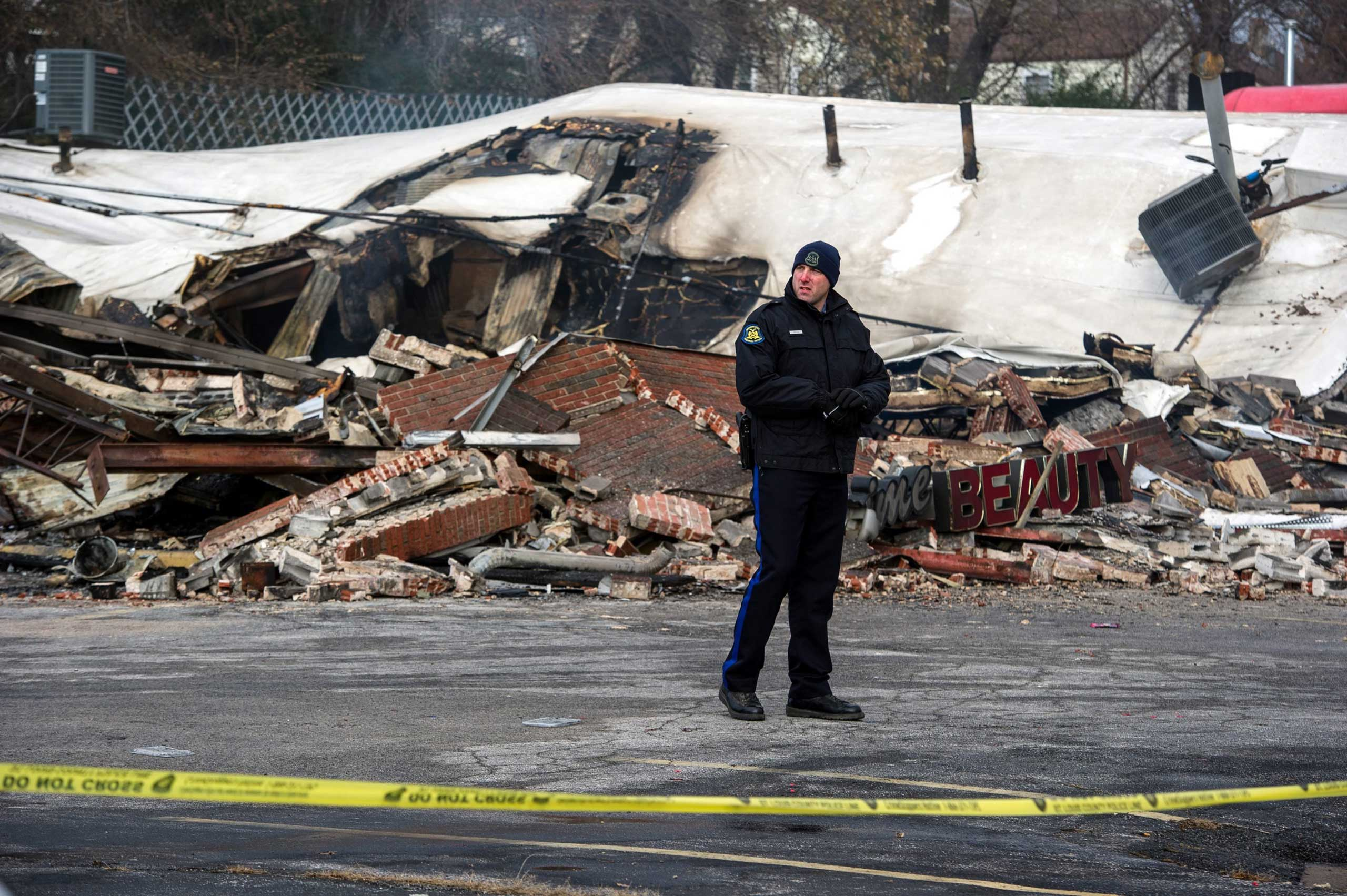 A policeman stands near one of the burnt businesses on West Florissant Avenue, which is closed for police investigation, in Ferguson, Mo. on Nov. 25, 2014.