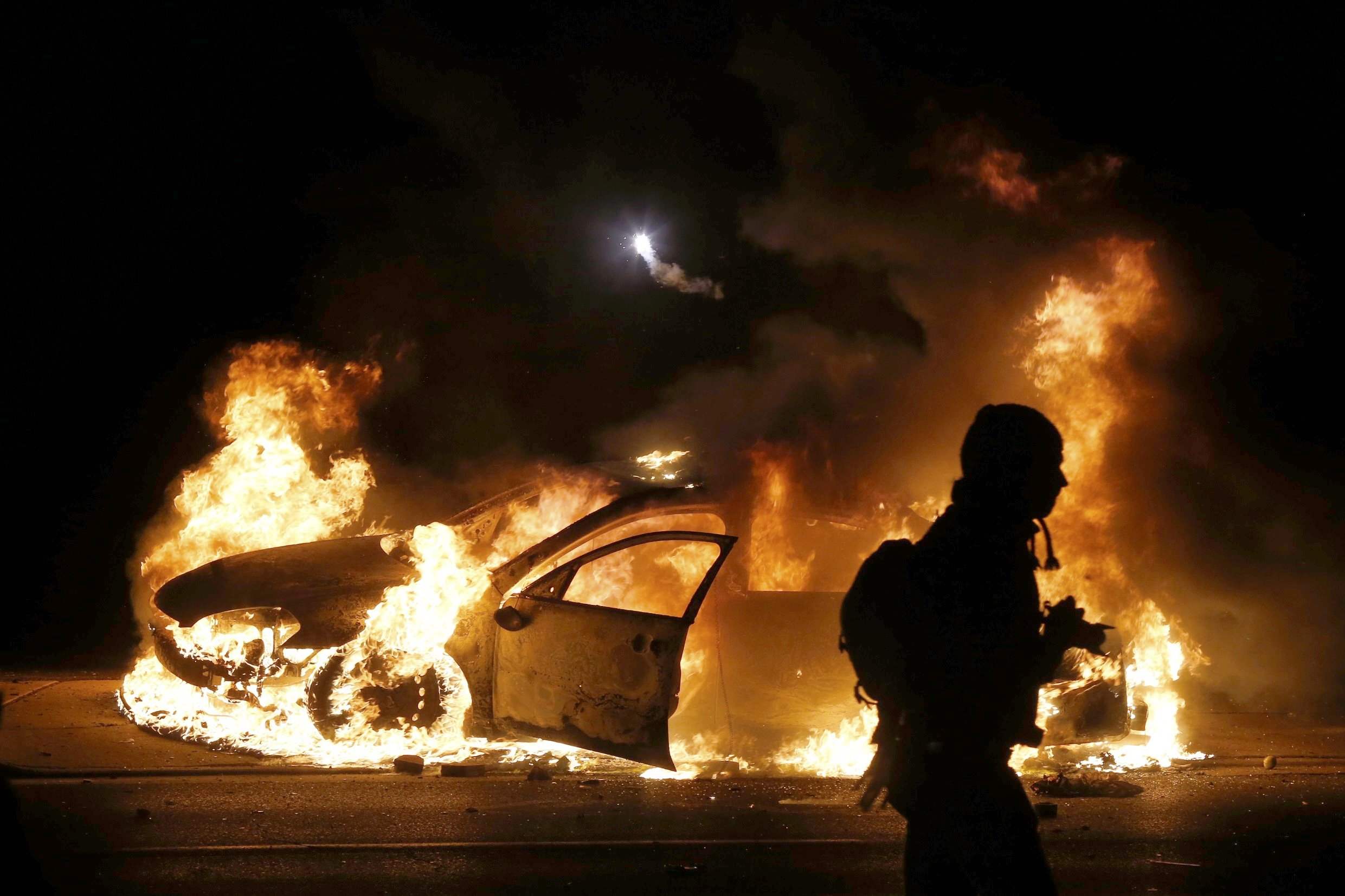 A car burns on the street after a grand jury returned no indictment in the shooting of Michael Brown in Ferguson, Mo. on Nov. 24, 2014.
