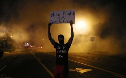 Aug. 17, 2014. A protester holds a sign towards the police after they shoot tear gas on W. Florissant in Ferguson. The protesters were throwing rocks and bottles towards the police.