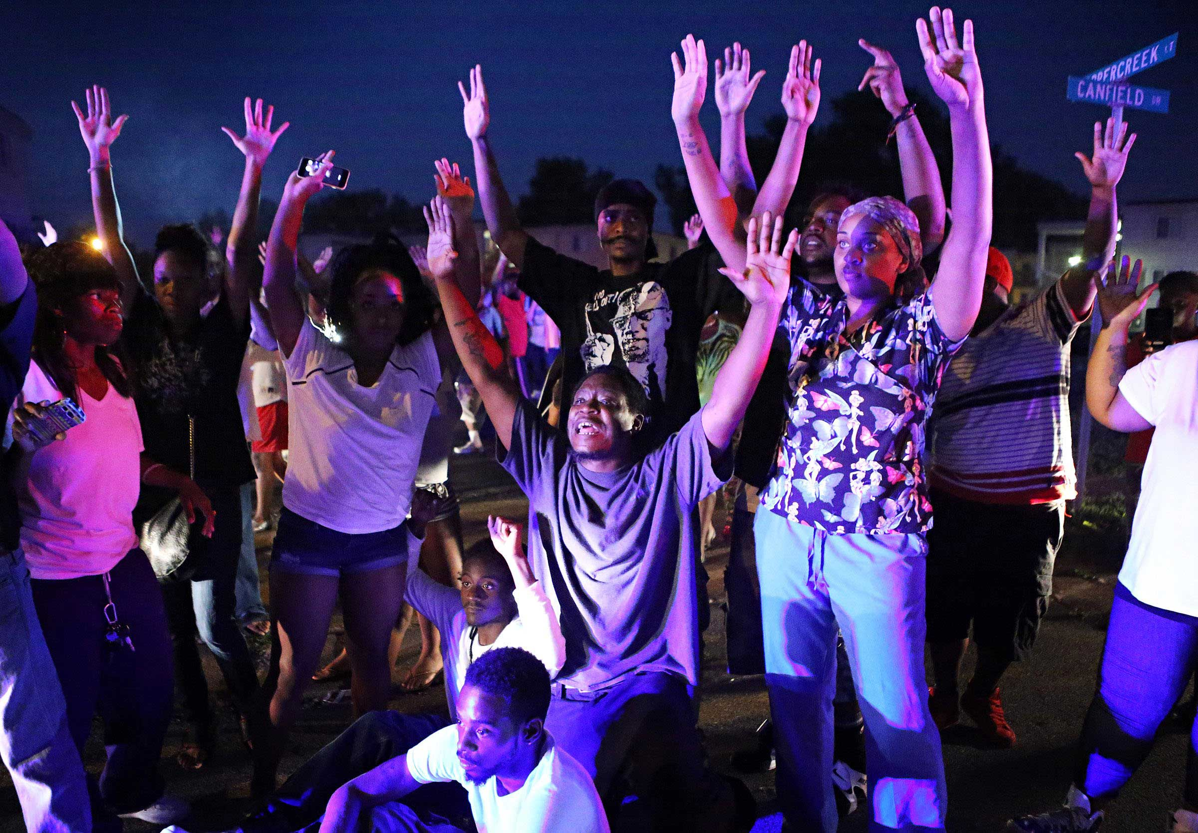 Aug. 9, 2014. A crowd gathers near the scene where 18-year-old Michael Brown was fatally shot by police in Ferguson, Mo., near St. Louis on Saturday. A spokesman with the St. Louis County Police Department confirmed a Ferguson police officer shot the man. The spokesman didn't give the reason for the shooting, nor provide the officer's name or race.