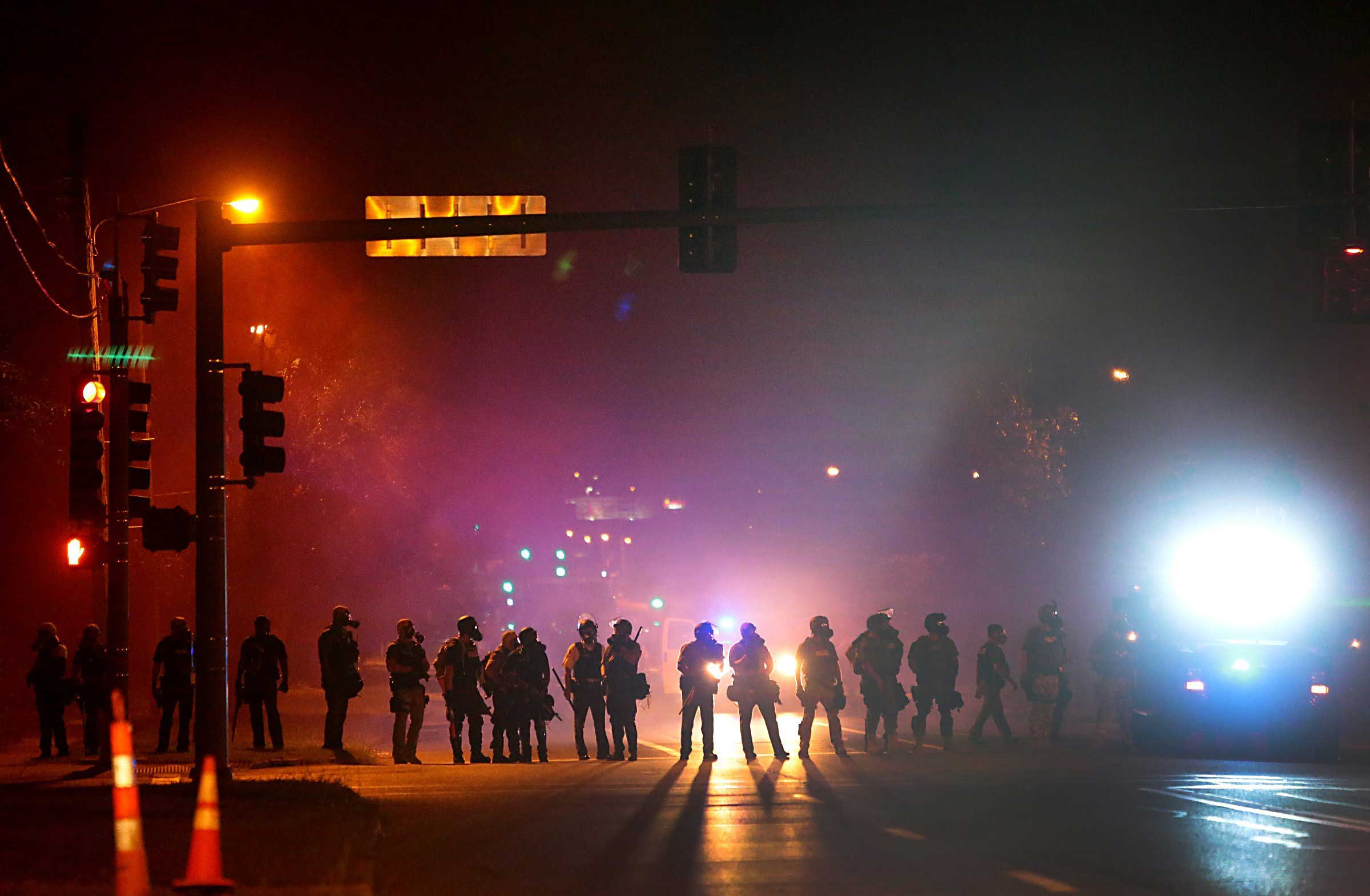Aug. 13, 2014. Tactical officers work their way north on West Florissant Avenue in Ferguson, clearing the road of residents, on Wednesday.