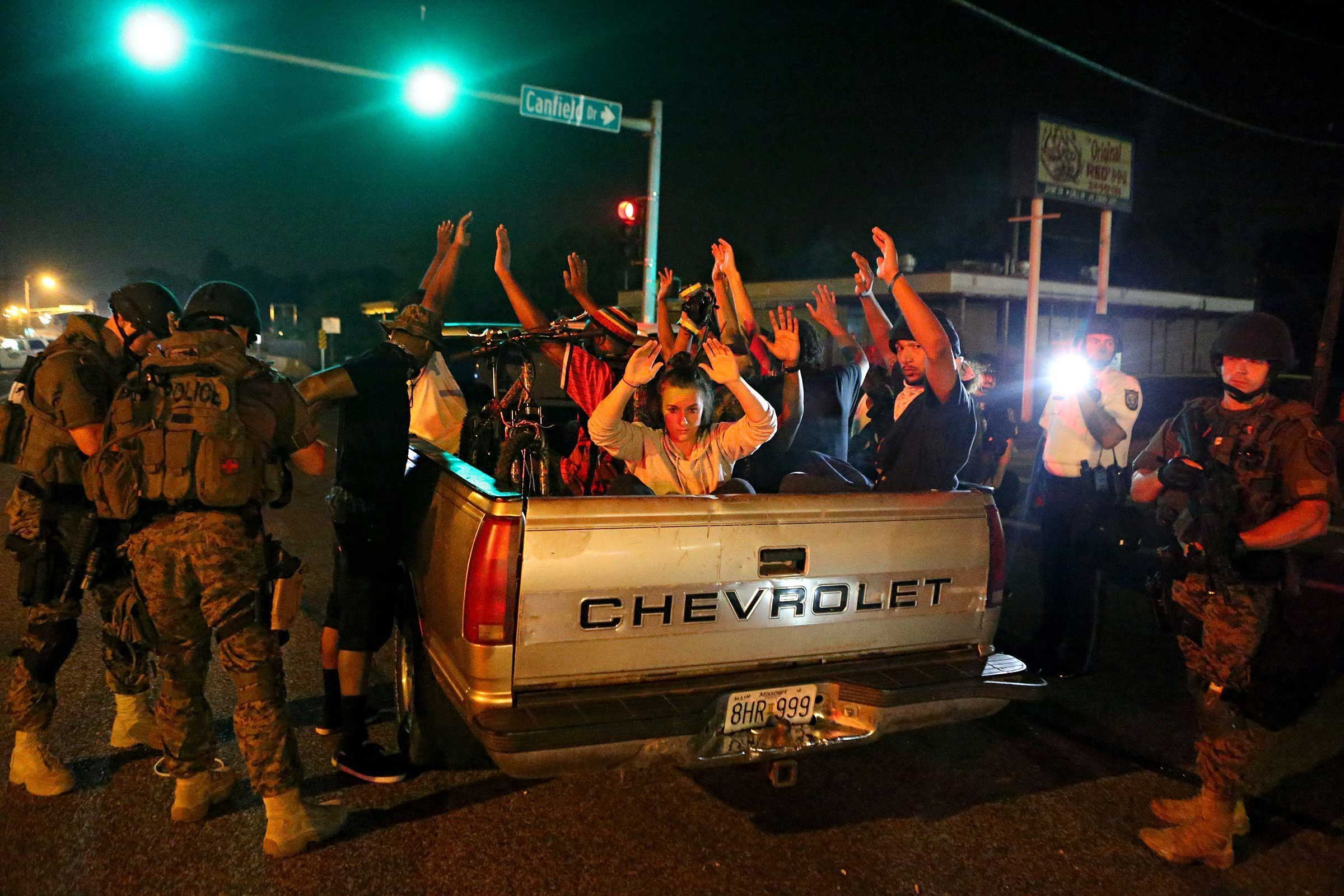 Aug. 19, 2014. Members of the St. Louis County Police tactical team take a truck load of 12 people into custody after they stopped it driving along W. Florissant Road near Canfield Drive. The police found two loaded guns on the people in the truck and removed an unused Molotov cocktail from the truck. Protests and clashes erupted between police and protesters in a Missouri city where racial tensions have boiled over since Ferguson police officer Darren Wilson fatally shot unarmed Black teen Michael Brown on Aug. 9.