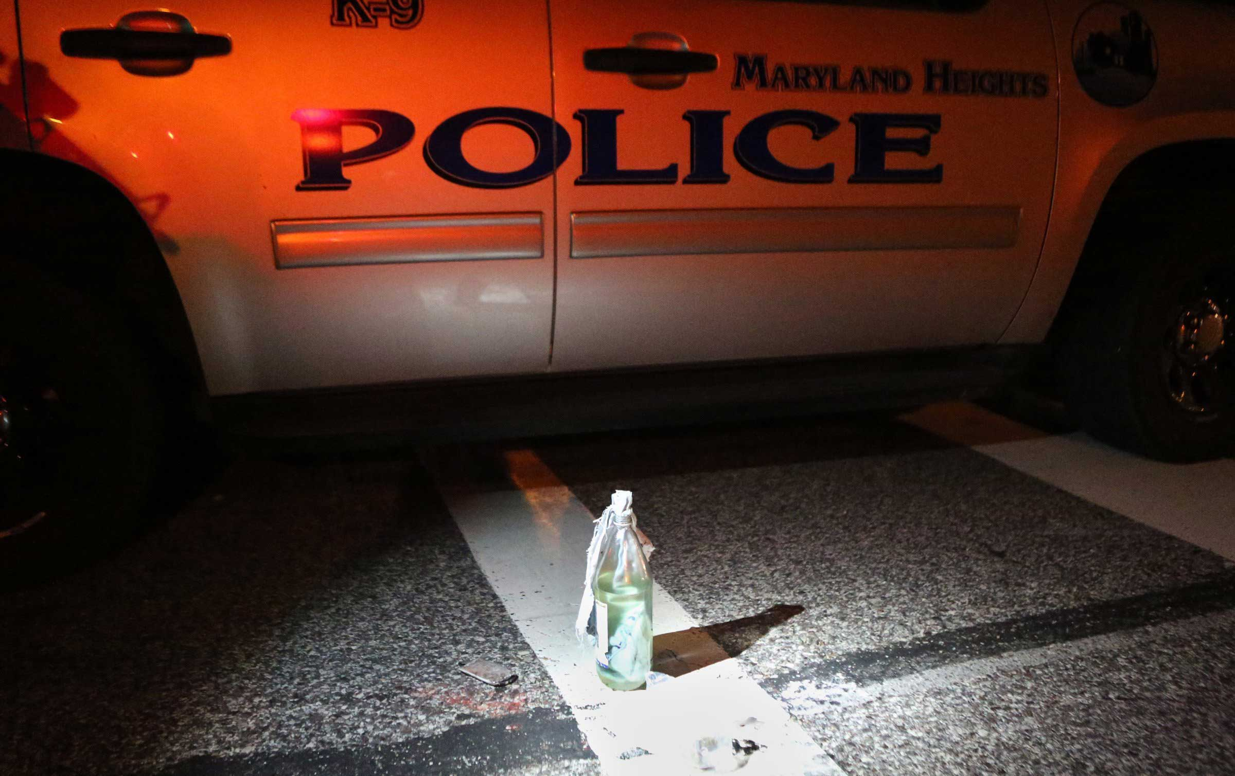 Aug. 19, 2014. A Molotov cocktail sits near a police car after it was removed from a truck carrying 12 people when it was stopped along W. Florissant Avenue near Canfield Drive. The police found two loaded guns on the people in the truck and removed an unused Molotov cocktail from the truck.