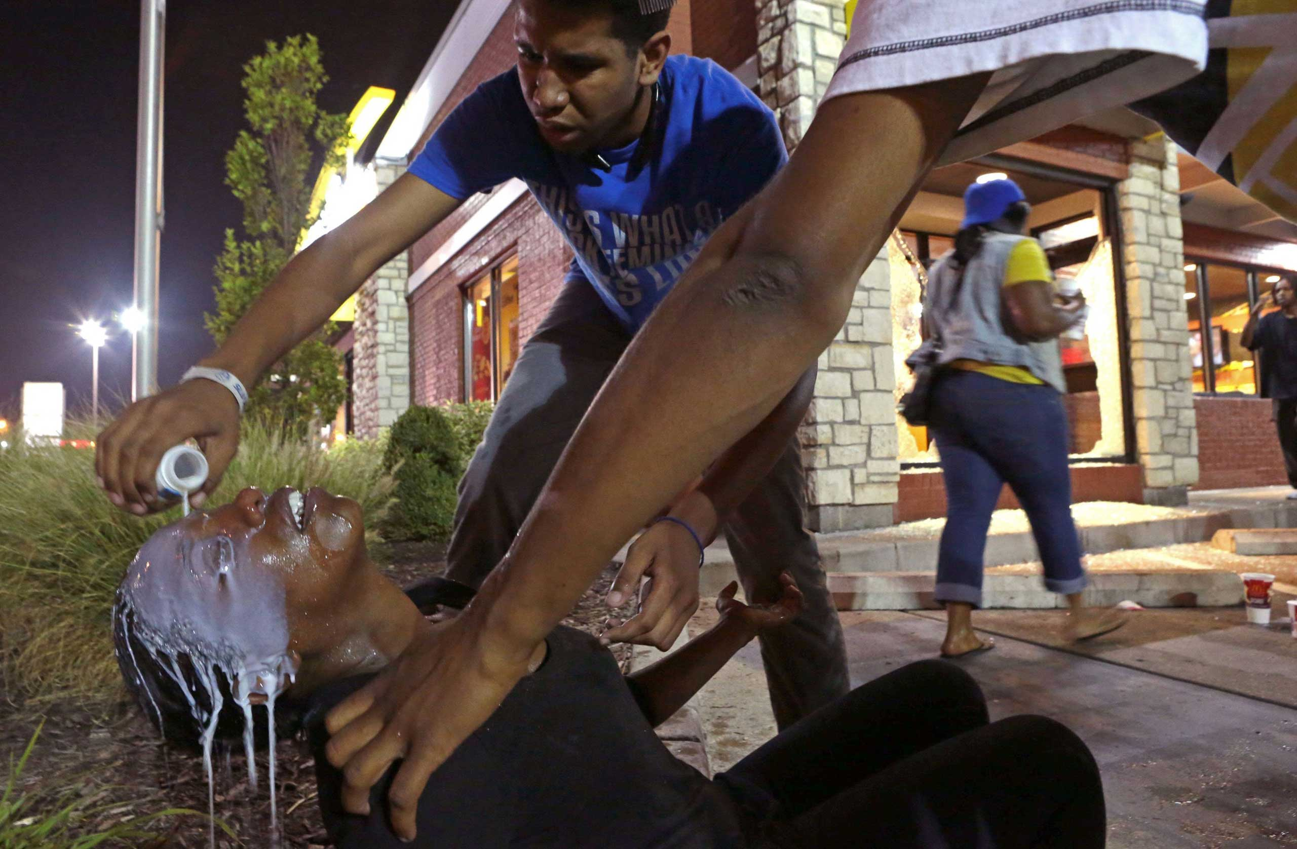 Aug. 17, 2014. Protesters help Cassandra Roberts, who was hit by tear gas on Sunday in Ferguson, Mo. They had broken into the McDonald's to get milk to wash the gas out of her eyes.  We thought it could be a peaceful night,  said Roberts, who was marching in Ferguson for the first time.  What the hell is going on in this world?