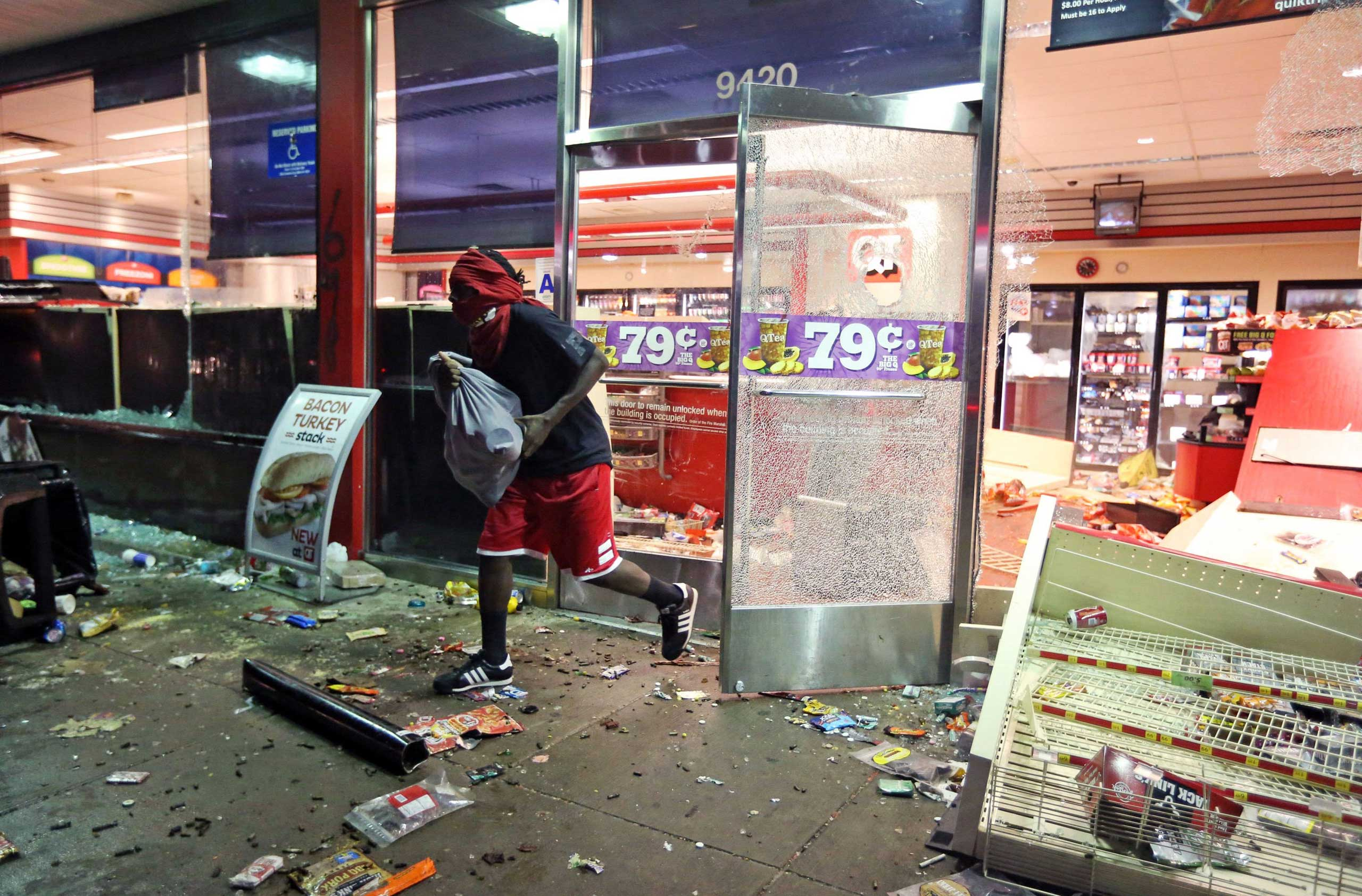 Aug. 10, 2014. A man leaves a store on Sunday, in Ferguson, Mo. A few thousand people crammed a suburban St. Louis street Sunday night at a vigil for unarmed 18-year-old Michael Brown who was shot and killed by a police officer, while afterward several car windows were smashed and stores were looted as people carried away armloads of goods as witnessed by an an Associated Press reporter.