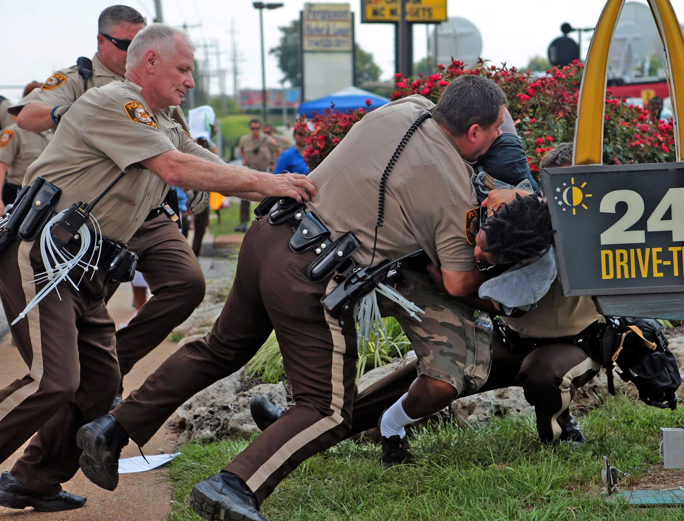 Aug. 18, 2014. Police tackle a man who was walking down the street in front of McDonald's on Monday. The man appeared to be walking past a group that had been assembled nearby and police were telling everyone to keep walking. Moments after he turned around and exchanged words with the police that he was just walking, police took him to the ground. Although there is no curfew in order tonight, police are strictly enforcing protestors to keep moving along the sidewalk or they are subject to arrest.