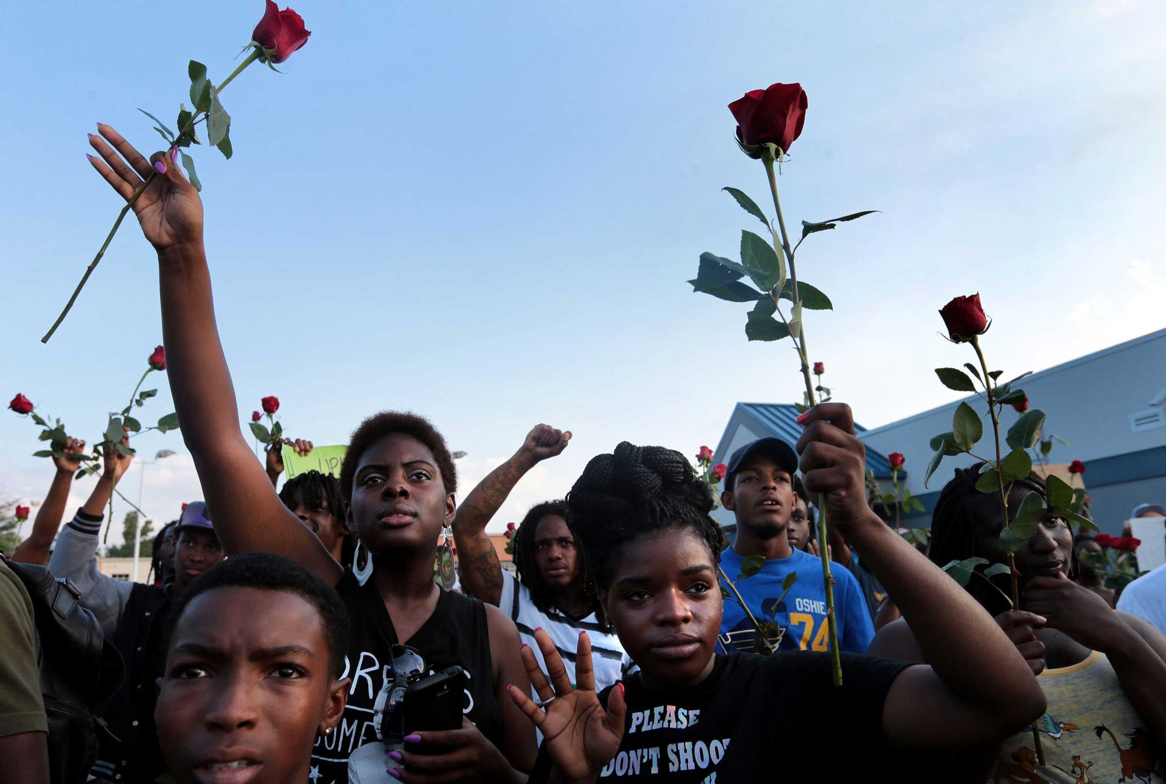 Aug. 18, 2014.  I am out here for justice; not just for Michael Brown, but for all of us,  said Krystal Harbor, 23, (third from left) who brought her brother Ray Clark,13, and friend Shylan Times to the protest Monday, Aug. 18, 2014, in Ferguson. Various volunteers passed out roses to those who marched on the sidewalk according to new guidelines set by police.