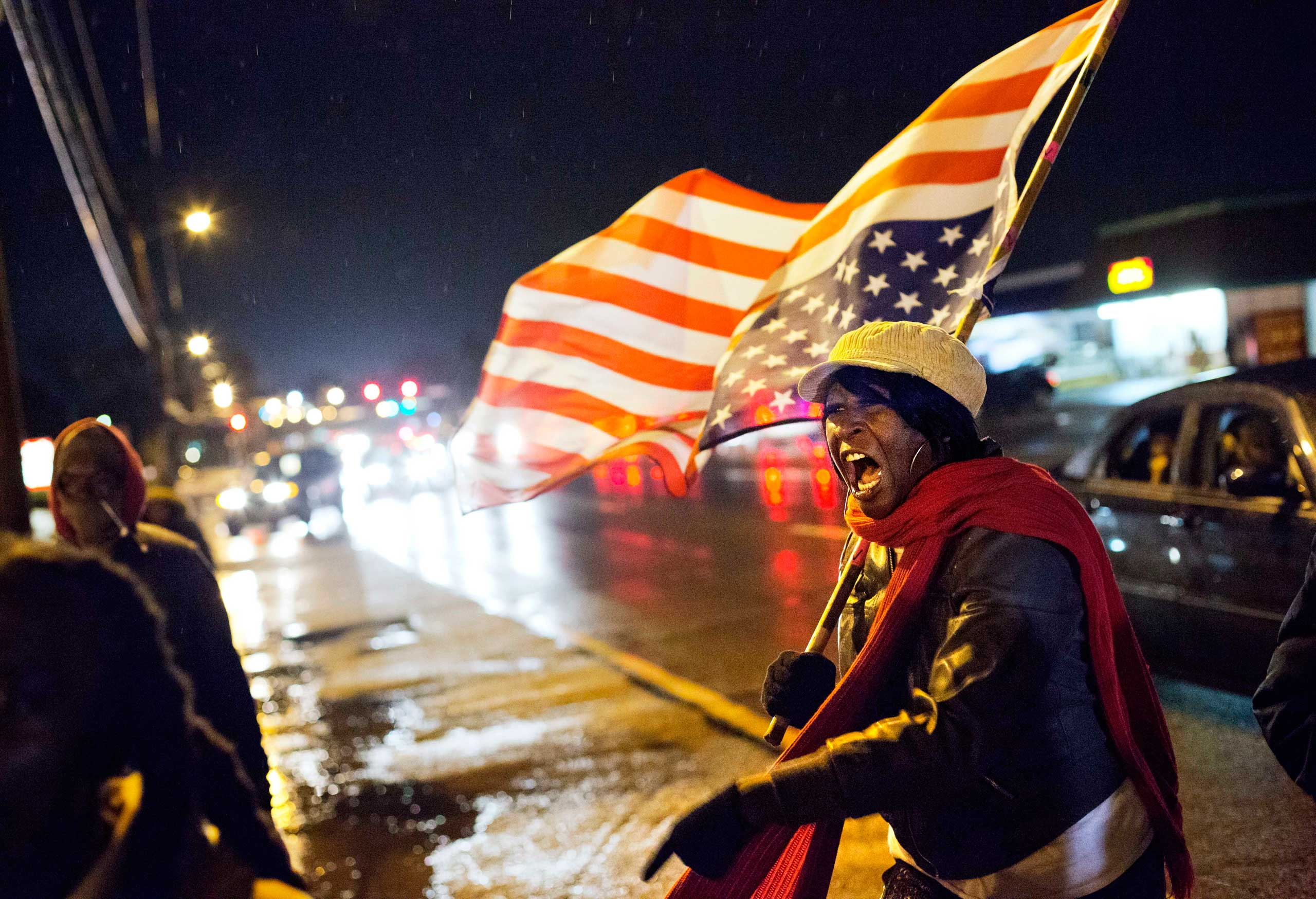 Gina Gowdy, of Ferguson, Mo., shouts while marching with protestors along a stretch of road where violent protests occurred following the August shooting of unarmed black teenager by a white police officer, Saturday, Nov. 22, 2014, in Ferguson, Mo.