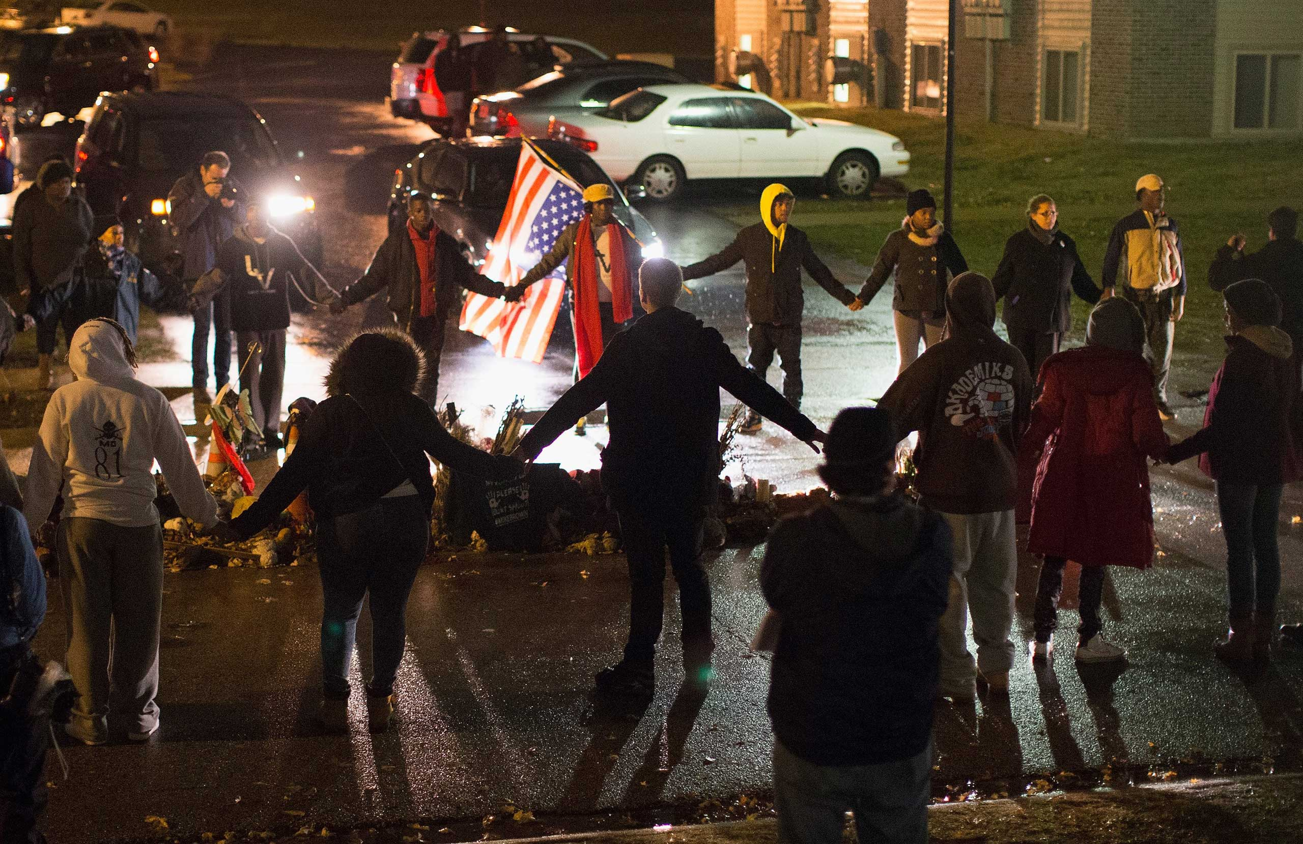 Demonstrators pray around a memorial at the spot where Michael Brown was shot to death on in Ferguson, Mo. on Nov. 22, 2014