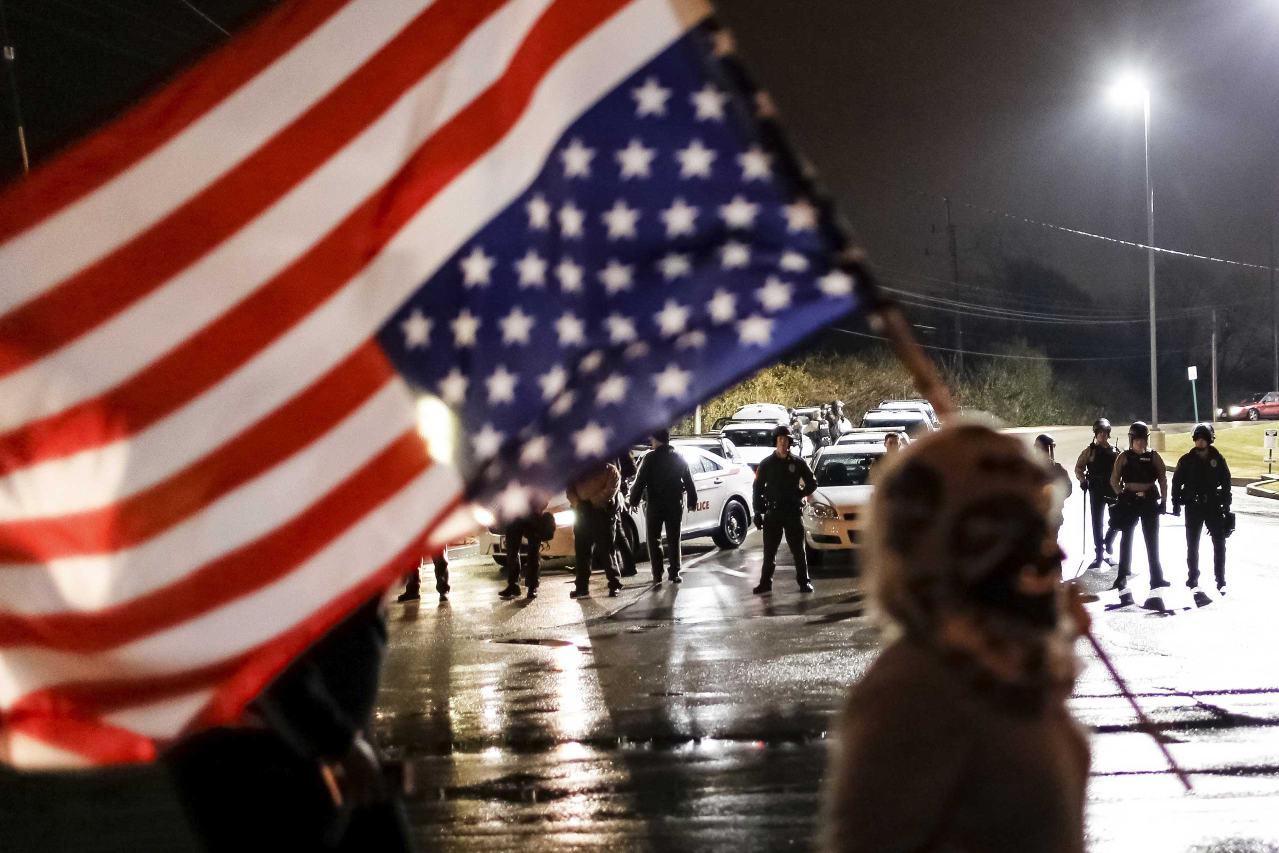 Police watch as a protester with an upside-down American flag marches along West Florissant Avenue in Ferguson, Mo., Nov. 22, 2014