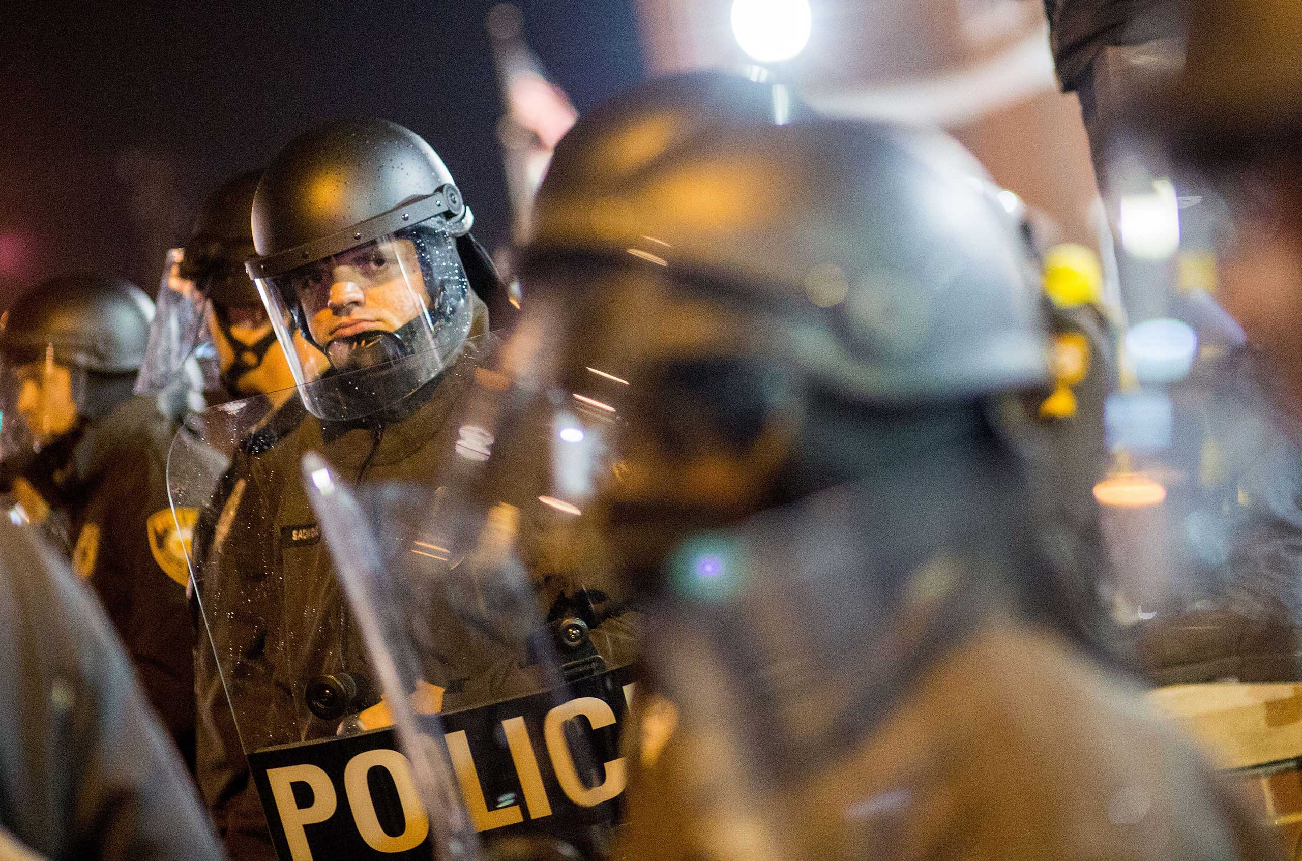 Police in riot gear observe protesters on the street near the Ferguson Police Station in Ferguson, Mo. on Nov. 23, 2014
