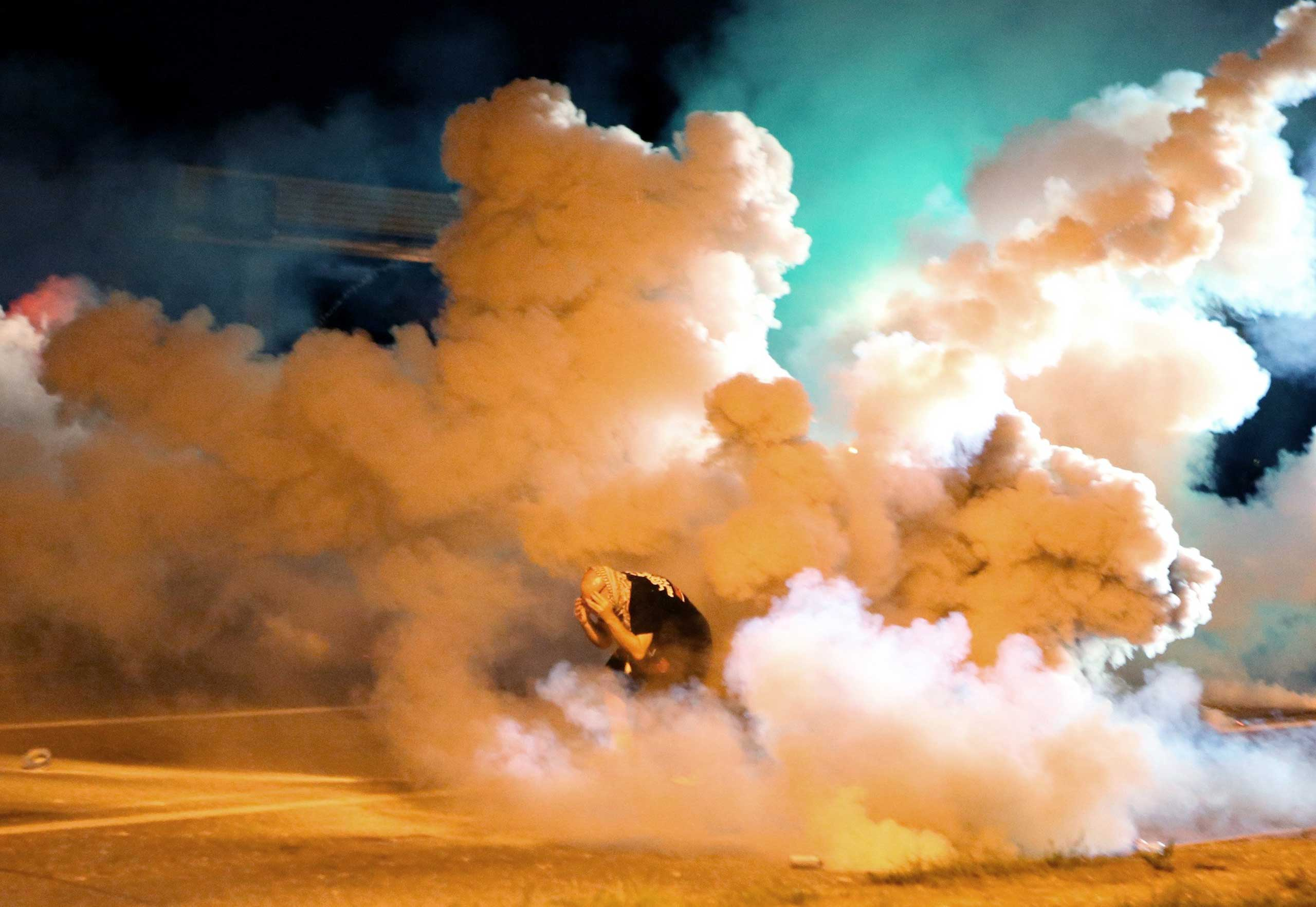 A protester takes shelter from billowing smoke during demonstrations in Ferguson on Aug. 13, 2014. Such scenes were relatively common during the first week of protests.