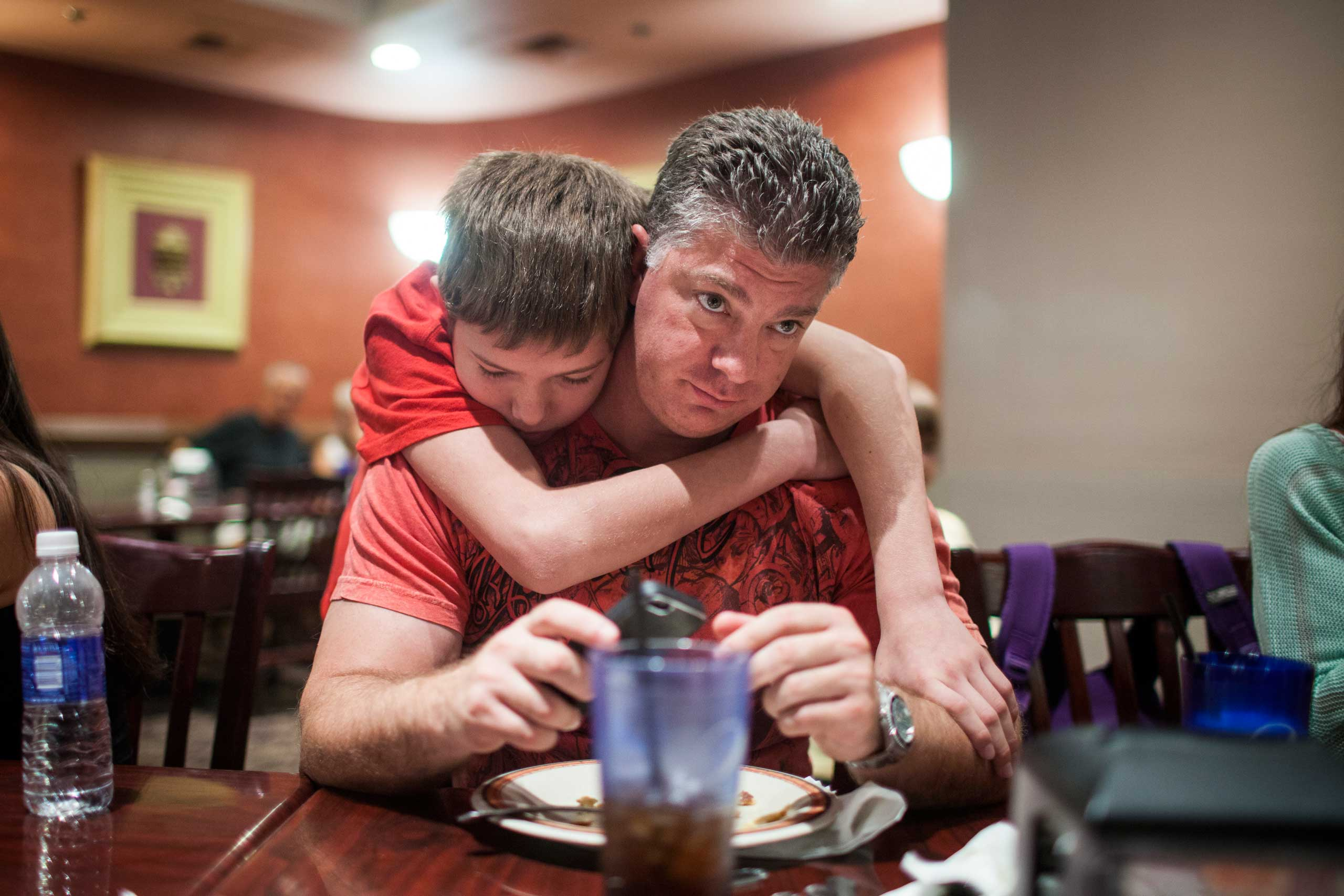 Mixed martial arts fighter Cade Rogue, 9, hugs his dad Jason, before fighting in the octagon in a United States Fight League All-star Pankration show at Blue Water Casino in Parker, Arizona, Oct. 2013.
