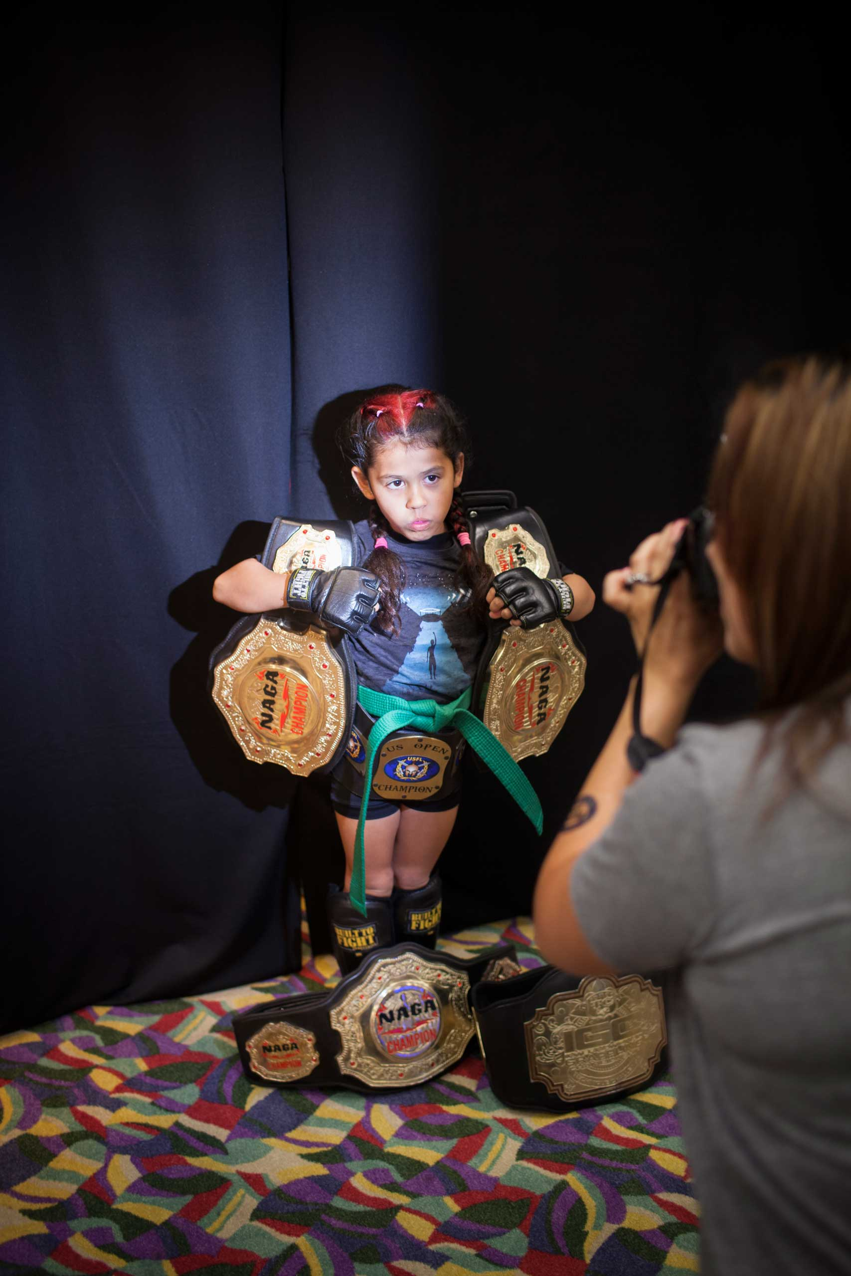 Regina  Black Widow  Awana, 7, with her Championship belts, posing for her sponsor at United States Fight League All-star Pankration show at Blue Water Casino in Parker, Arizona, Oct. 2013.