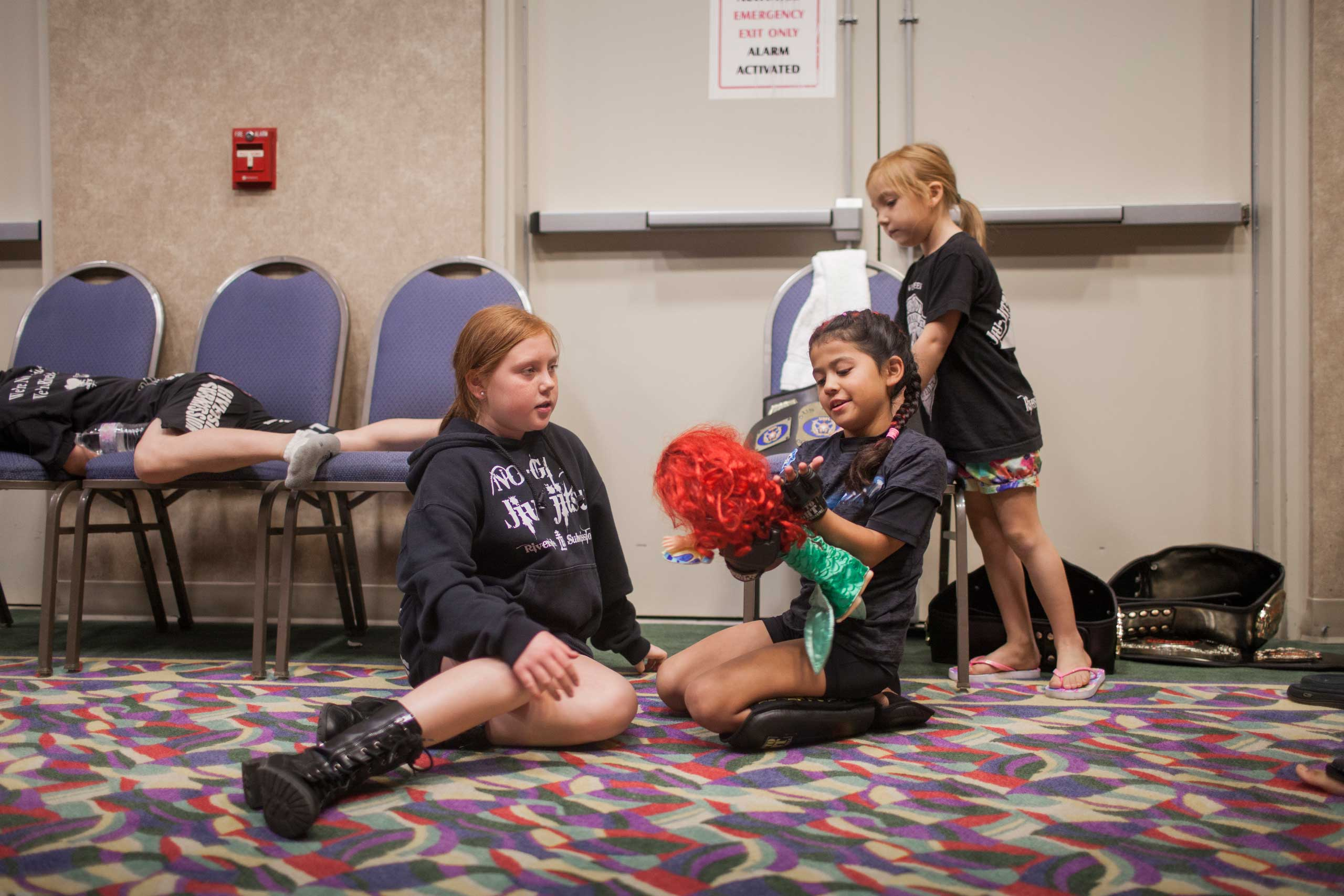 Regina  Black Widow  Awana, 7, playing with her favorite doll, Ariel, with friends before her fights. She won all fights this night. United States Fight League All-star Pankration show at Blue Water Casino in Parker, Arizona, Oct. 2013.