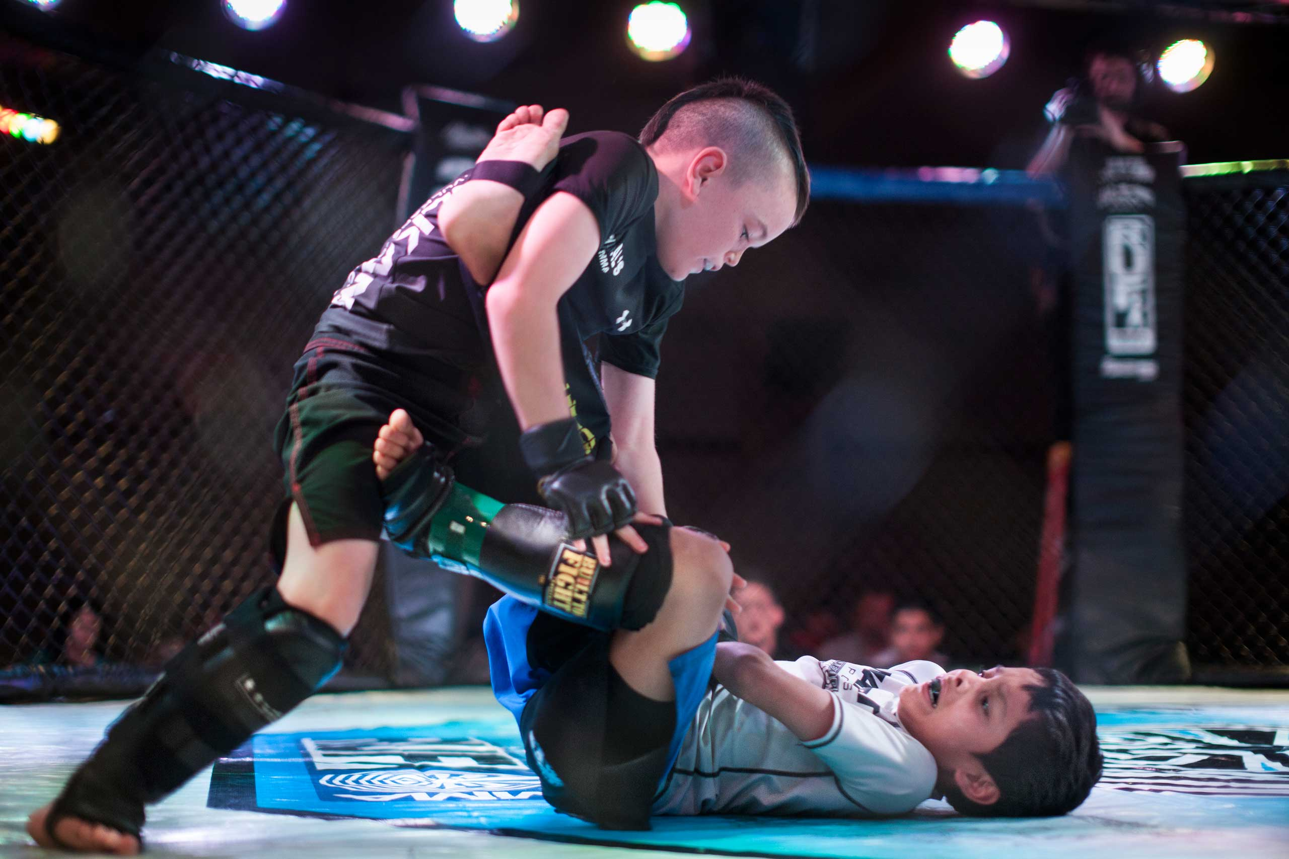 Mixed martial arts fighters Justin Ramirez, 7, and Chris Arrey, 7, fighting in the octagon in United States Fight League All-star Pankration show at Blue Water Casino in Parker, Arizona, Oct, 2013.