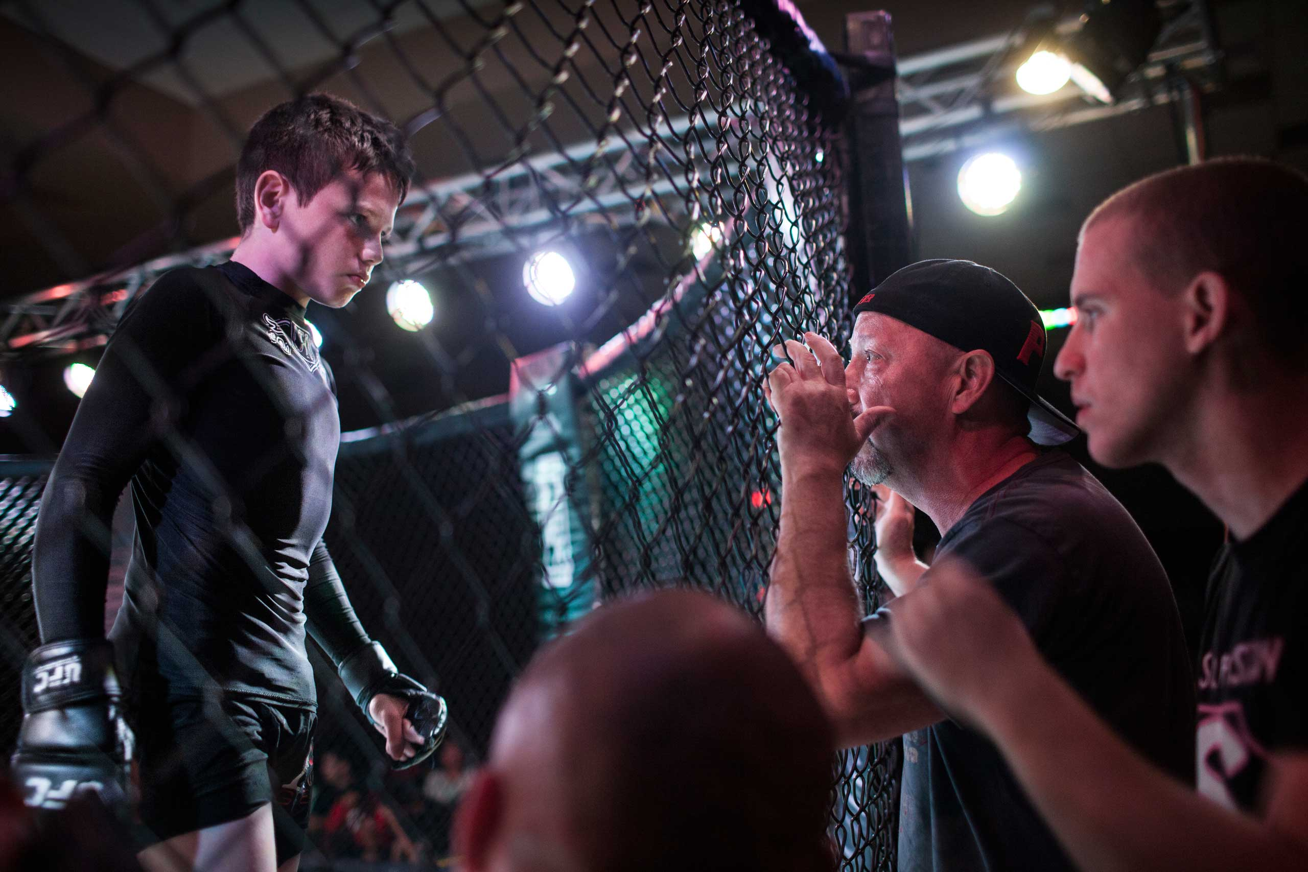 Mixed martial arts fighter Brock Locnikar, 8, in the octagon, takes precious advise from his corner men Clay Carpenter and Thiago Azeredo during United States Fight League All-star Pankration show at Blue Water Casino in Parker, Arizona,  Oct. 2013.