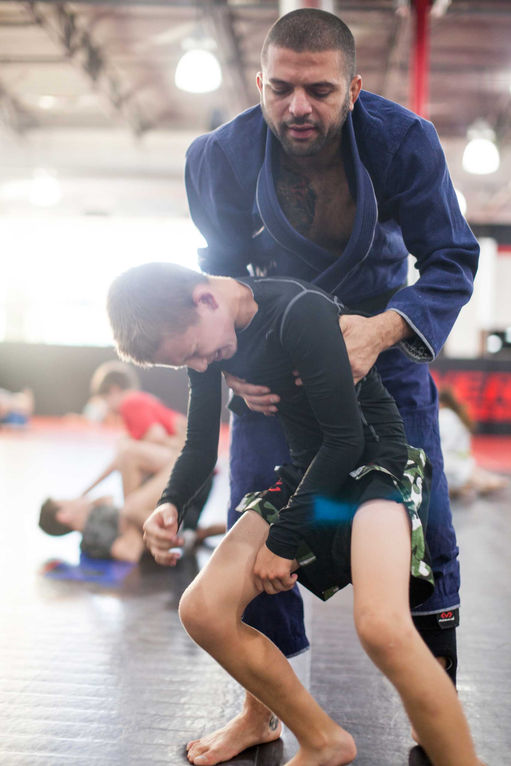William Reid, 10, picked up by his coatch Andre Maracaba at a practice at Power mixed martial arts  gym in Phoenix, Arizona. Some times whilst training, kids might sprain a limb, but some times it's just mental stress and tiredness that triggers them in to tears, Oct. 2013.