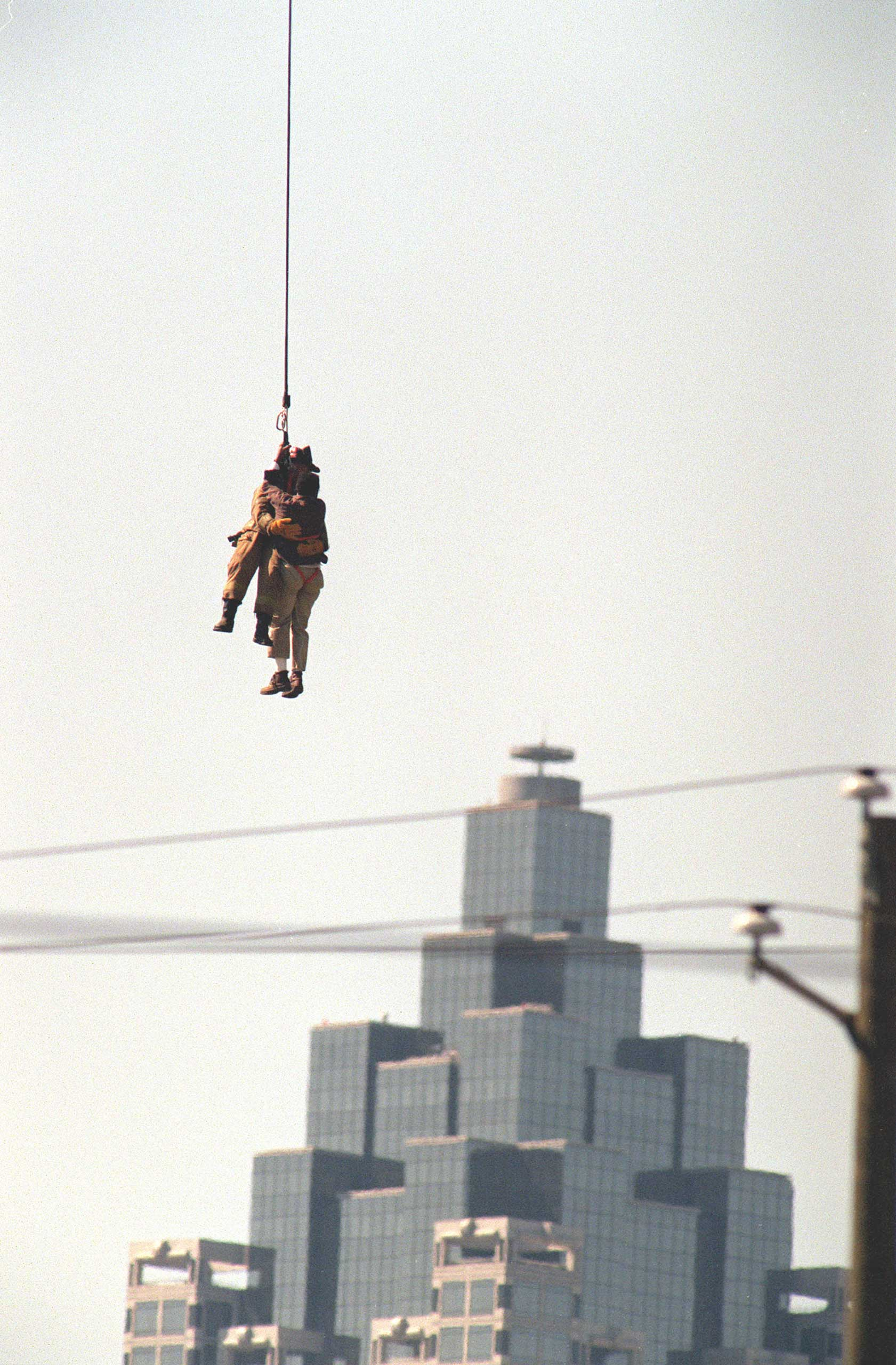 A firefighter dangles from a helicopter to rescue a stranded crane operator in Atlanta in 1999.
