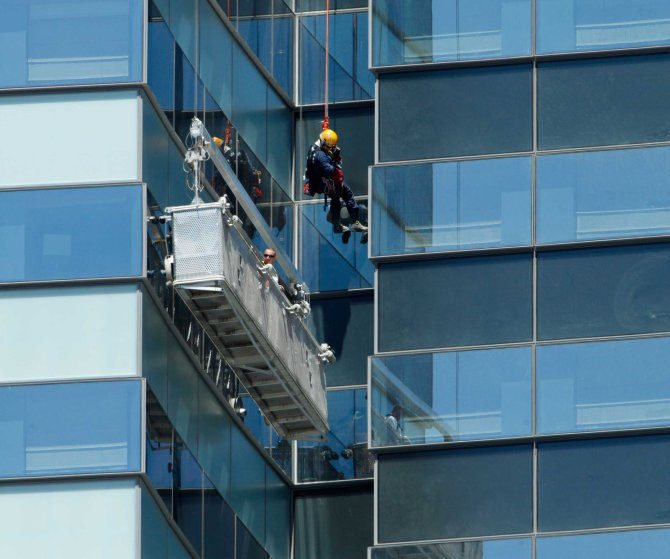 A Las Vegas Fire Department high-angle rescue worker lowers down to window washers who are stranded outside the 35th floor of the Vdara Hotel at CityCenter in Las Vegas on July 25, 2012.