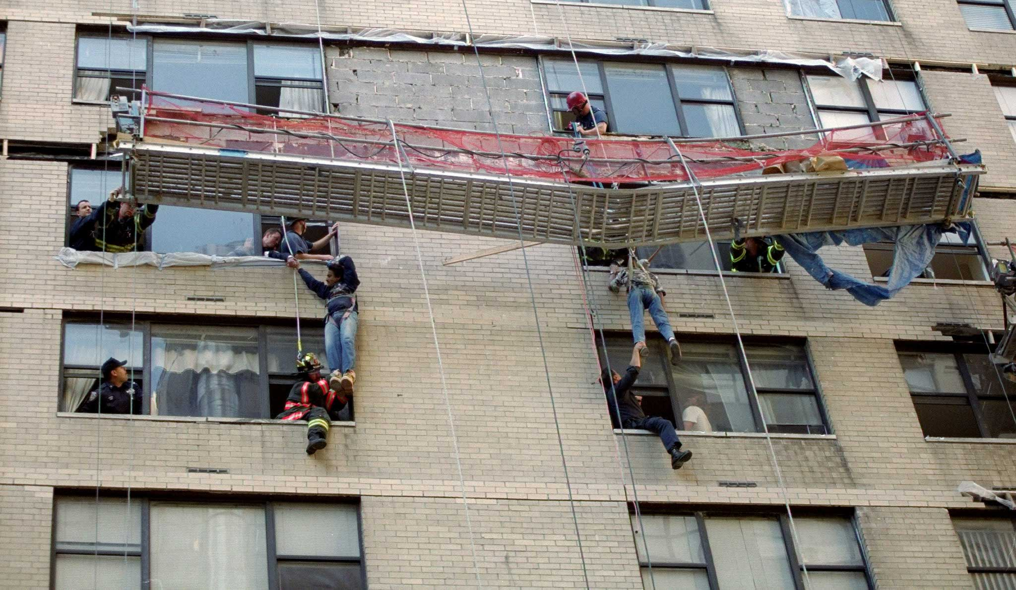 Firefighters rescue two construction workers dangling 8 floors off the ground from a building in Midtown Manhattan in New York City on Oct. 12, 1999.