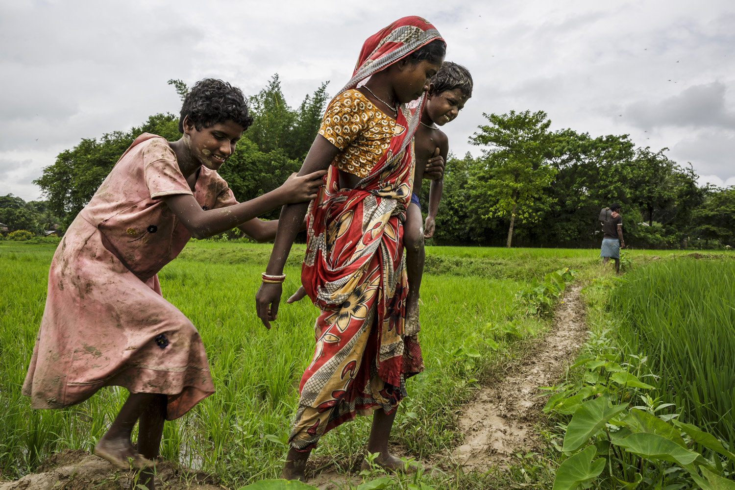 Sonia and Anita Singh follow their mother on her through fields, Oct. 19, 2013 in West Bengal, India.