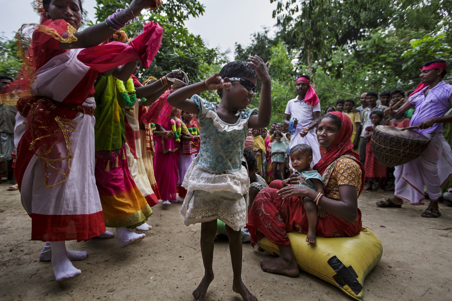 Anita joins in the celebrations as she and her sister Sonia return home to their rural village on Oct. 27, 2013 in West Bengal, India.