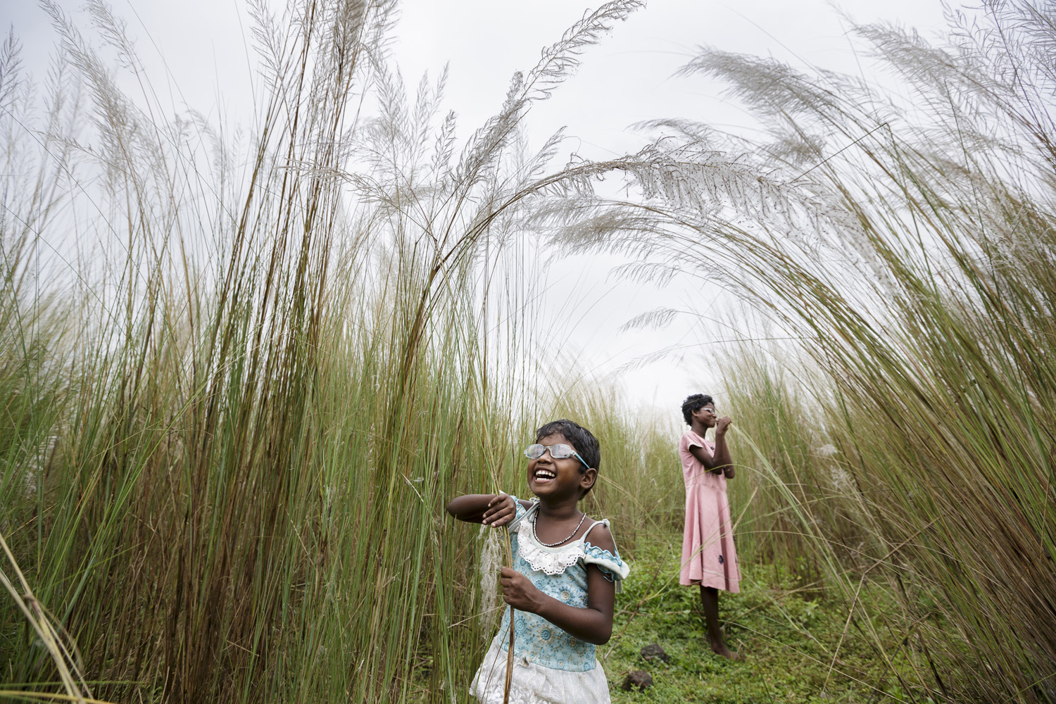 Anita and Sonia explore some of their first sensations of sight after their surgery, as they walk through bulrushes near their village, Oct. 28, 2013 in West Bengal, India.