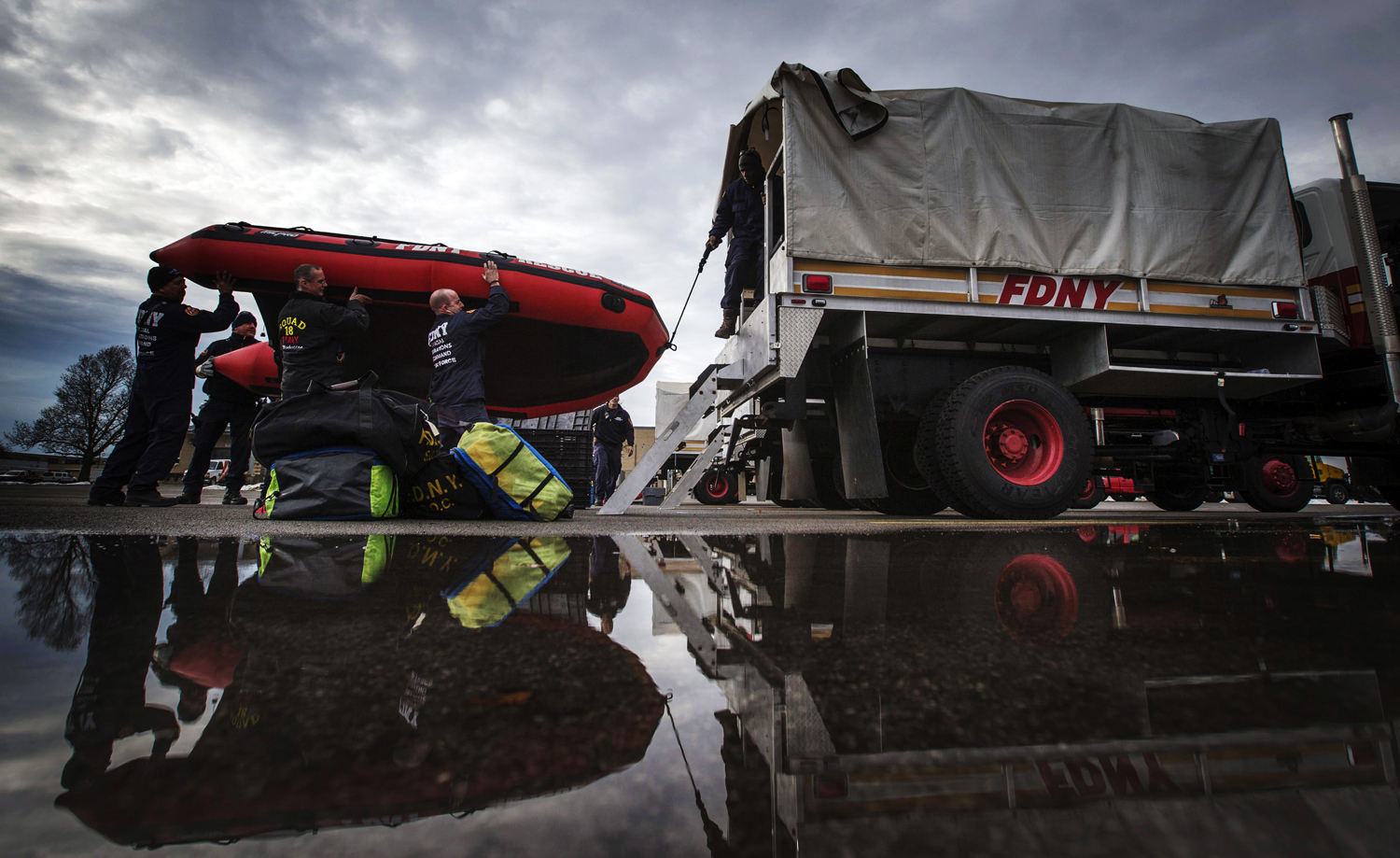 Firefighters from New York City load a rescue boat to prepare for possible flooding following a massive snow storm in Williamsville, New York on November 23, 2014.