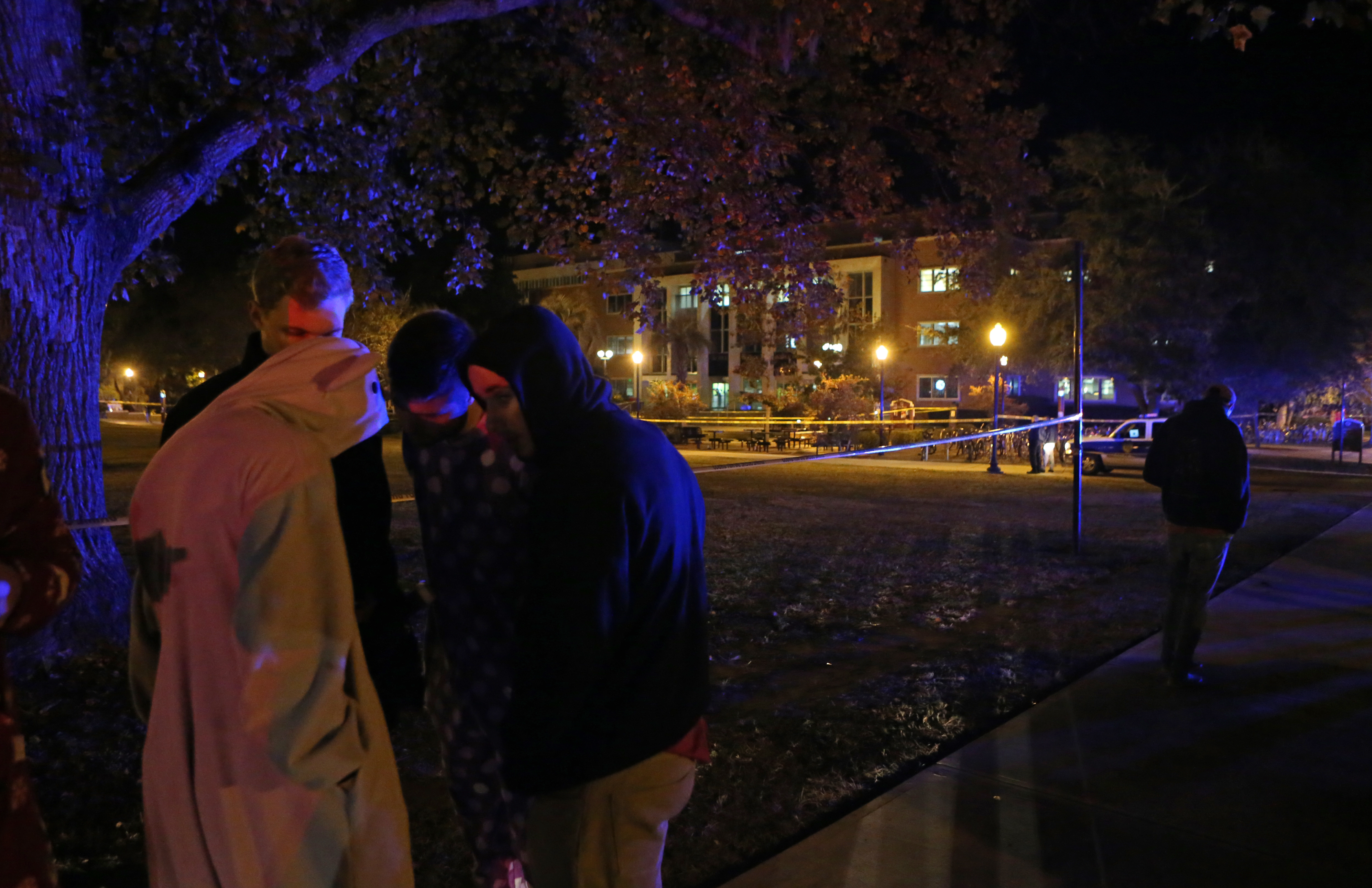 Students call their friends still locked down in Strozier Library after a shooting at Florida State University in Tallahassee, Fla., on Nov. 20, 2014