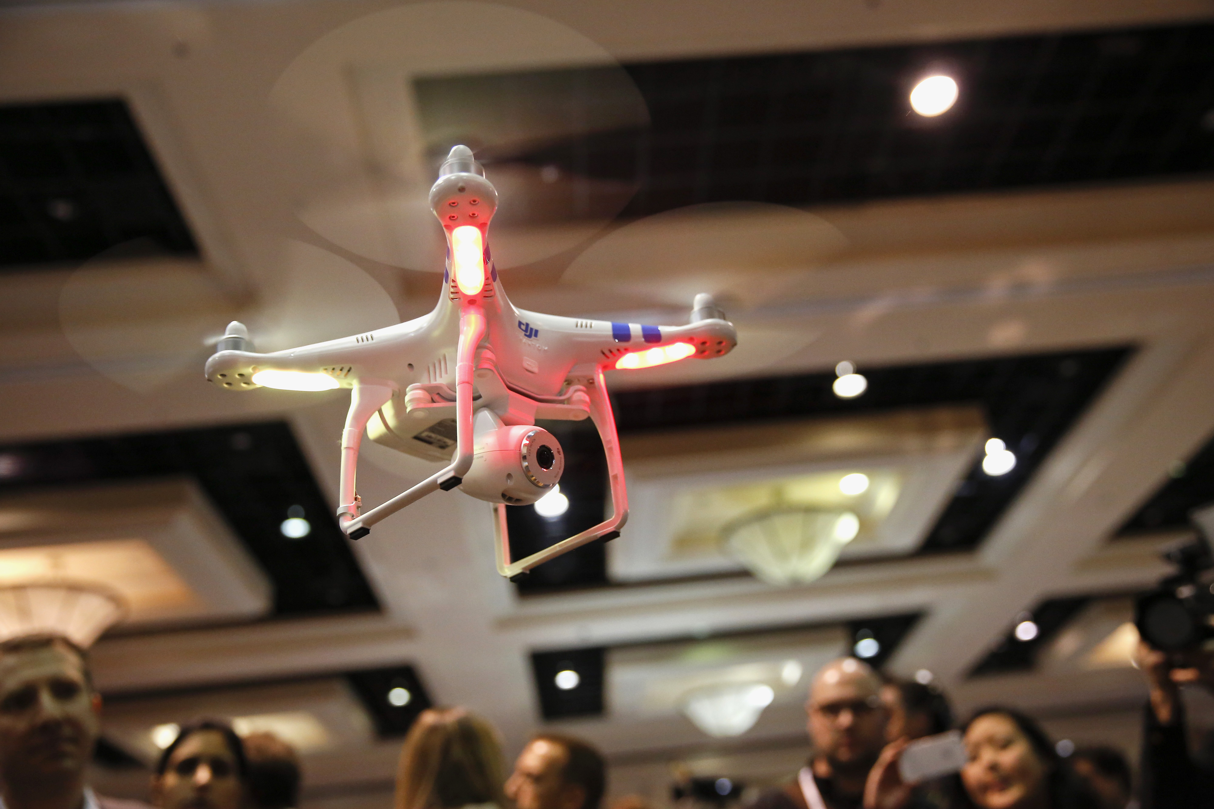 A DJI Innovations Phantom remote-controlled drone hovers above attendees during the CES Unveiled press event prior to the 2014 Consumer Electronics Show in Las Vegas, Nevada, U.S., on Sunday, Jan. 5, 2014.